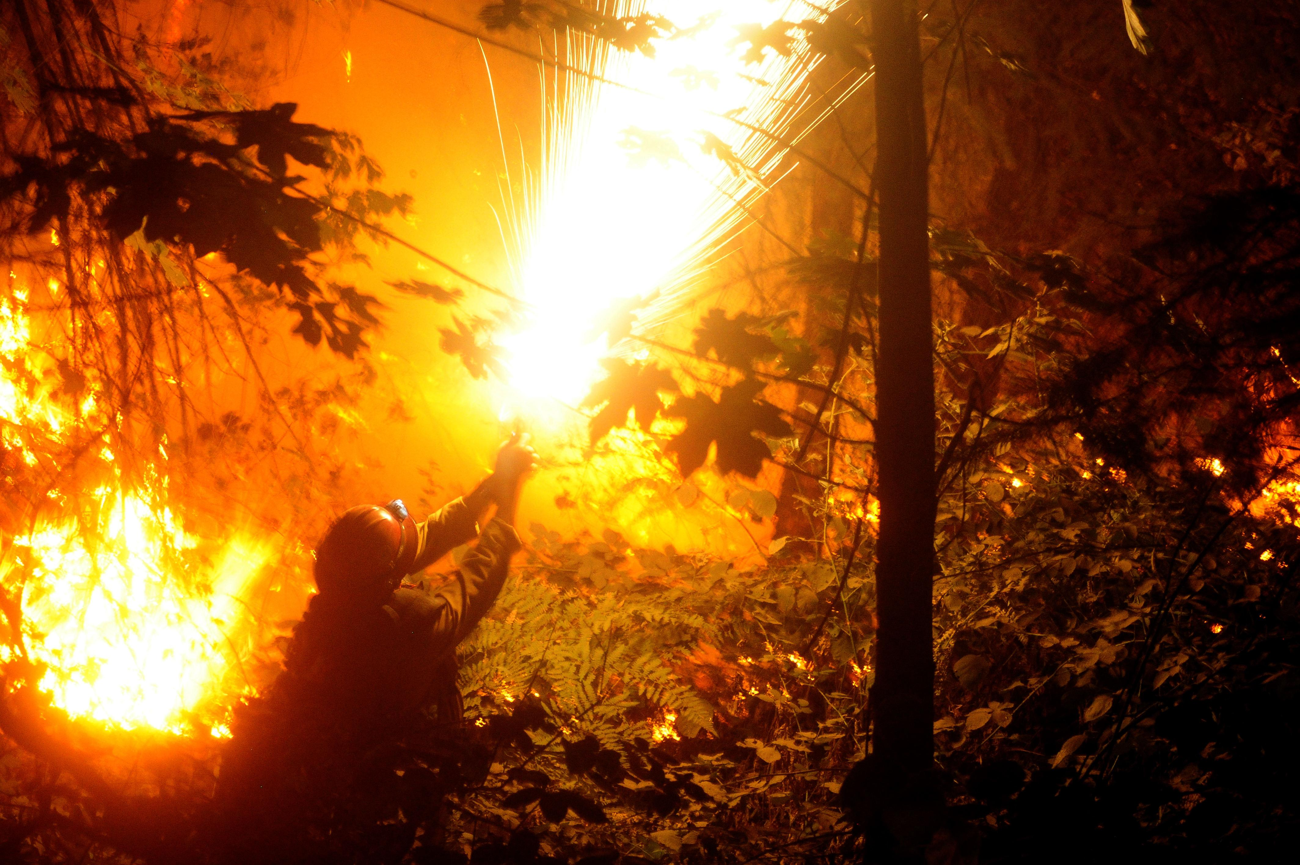 <p>A U.S. Forest Service Laguna Hotshot uses a flare gun to start a controlled burn along a steep slope at the Delta Fire in Redding, Calif., Sept. 6, 2018. (Photo: Neal Waters/ZUMA Wire) </p>