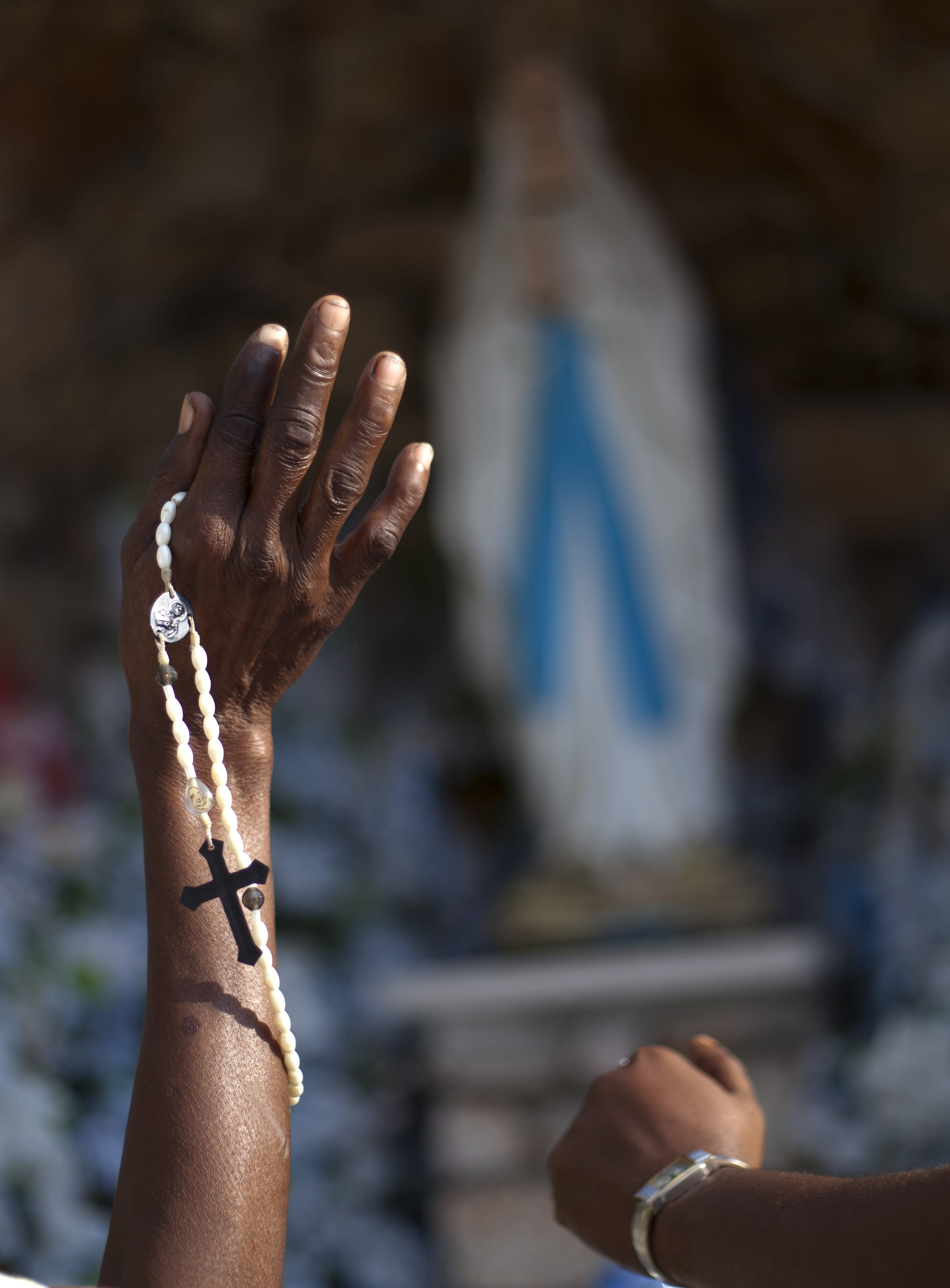 A woman holds up her rosary wrapped hand in praise in front of a statue of the Virgin Mary at Saint Yves Catholic church in Port-au-Prince, Haiti. Thursday, March 14, 2013. Latin Americans reacted with joy on Wednesday at news that Pope Francis, Argentina's former cardinal Jorge Mario Bergoglio, had become the first pope ever from the Americas. Francis began his first day as pope, on Thursday, making an early morning visit in a simple Vatican car to a Roman basilica dedicated to the Virgin Mary and prayed before an icon of the Madonna. (AP Photo/Dieu Nalio Chery)