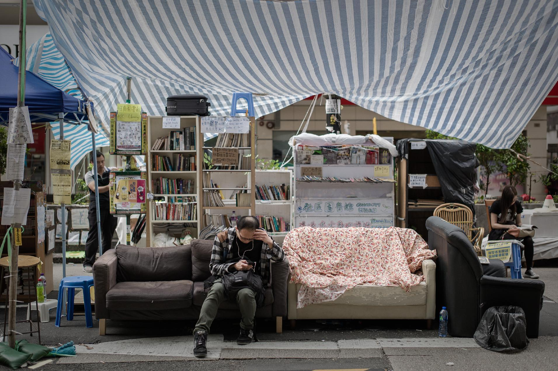 A man checks his mobile phone as he sits on a sofa at an encampment of pro-democracy protesters in the Mongkok district of Hong Kong on November 12, 2014 (AFP Photo/Philippe Lopez)