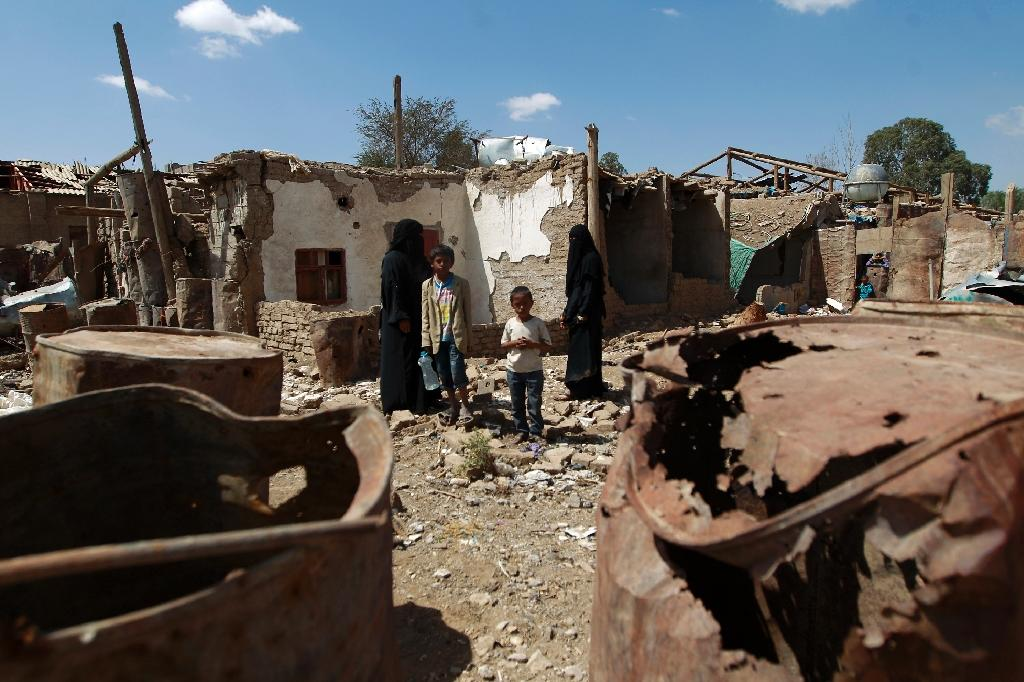 A Yemeni family stands outside their house which was damaged in an air-strike by the Saudi-led coalition at a slum in the capital Sanaa, in March 2016 (AFP Photo/Mohammed Huwais)