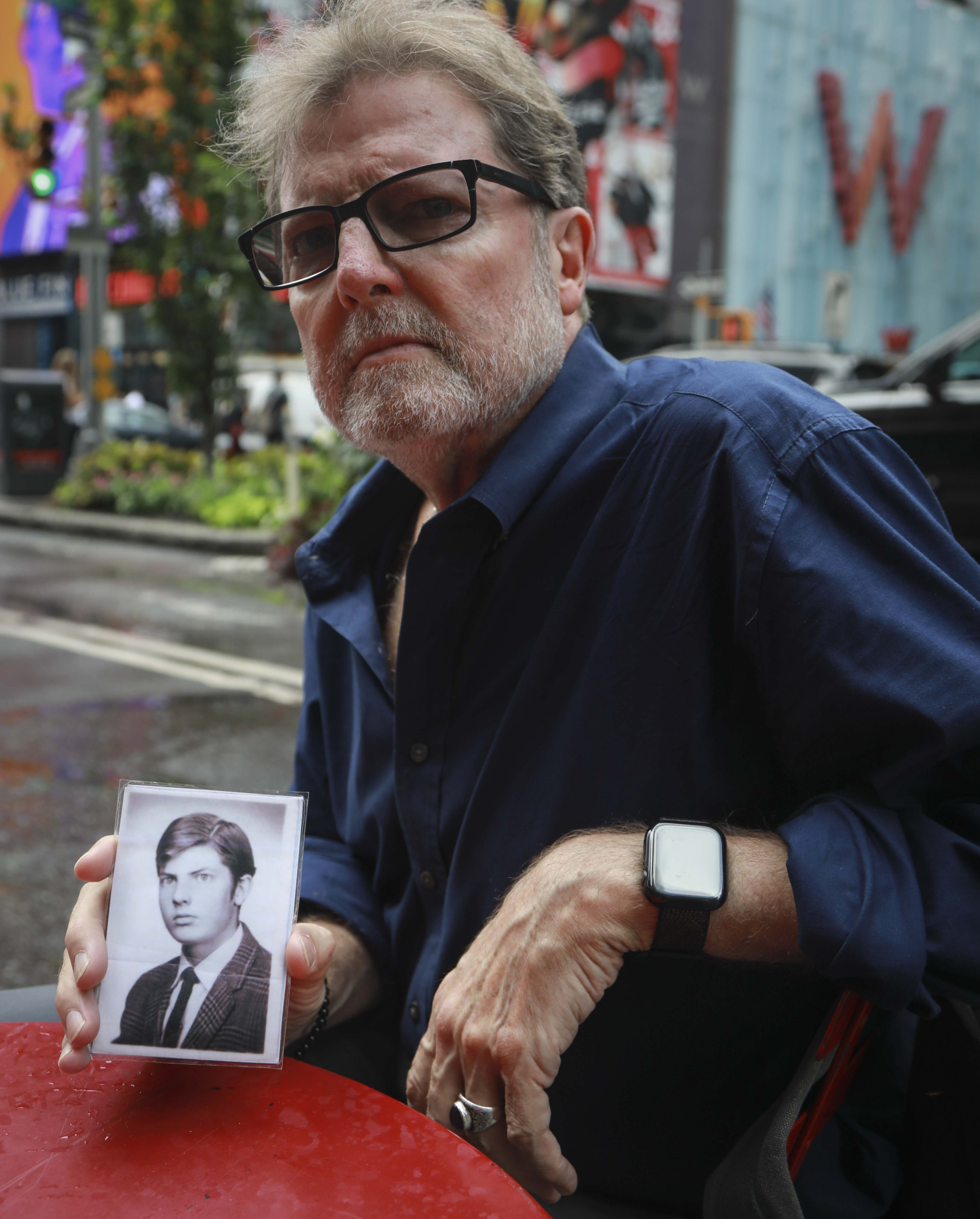 This Wednesday, Aug. 7, 2019 photo shows Brian Toale, holding a photo of himself at 16 years old in New York. Thousands of people who say they were molested as children in New York state will head to court this week to file lawsuits against their alleged abusers and the institutions where they worked. Toale, 66, who says he was molested by an employee at a Catholic high school he attended on Long Island, was one of the leaders in the fight to pass the Child Victims Act. (AP Photo/Bebeto Matthews)