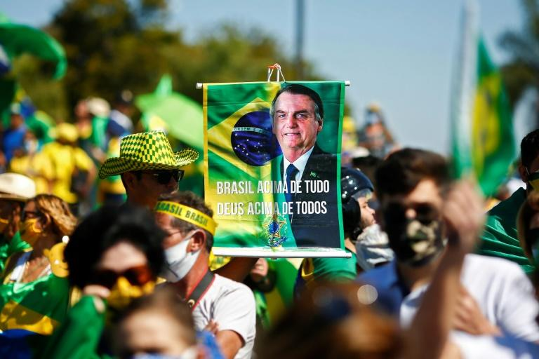 "A supporter brandishes a banner showing Brazilian Jair Bolsonaro, who has repeatedly evoked the threat of a ""coup"""