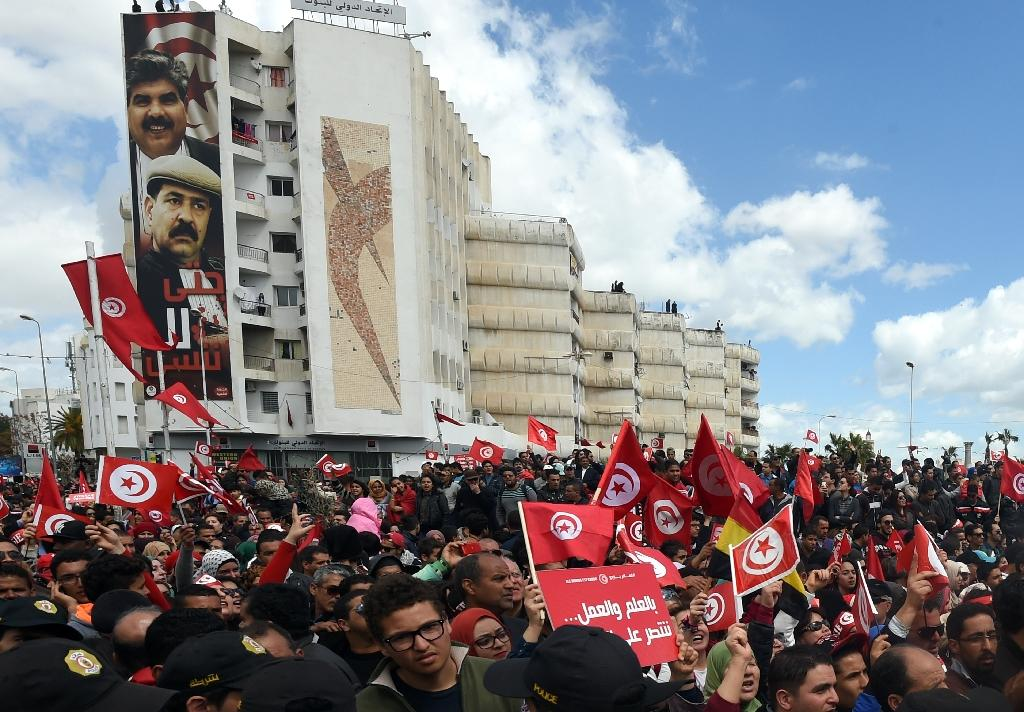 Tunisians wave their national flag during a march against terrorism outside Tunis' Bardo Museum on March 29, 2015 (AFP Photo/Fethi Belaid)