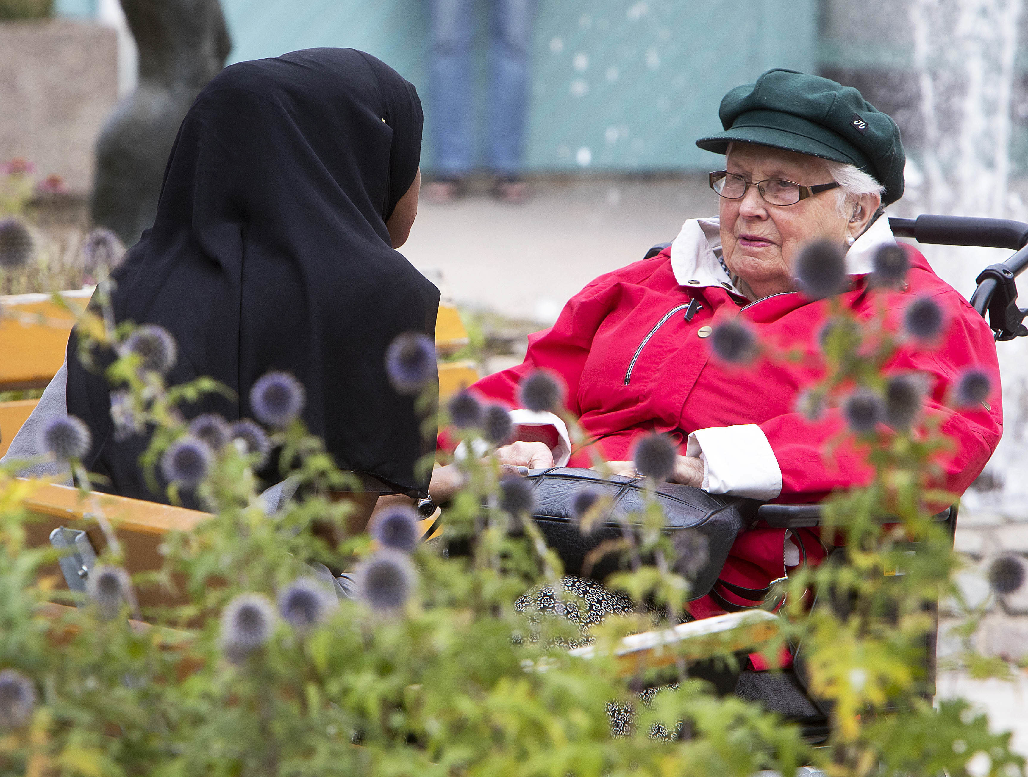 In this Aug. 30, 2018 photo a young migrant from Africa talks to an old woman she is taking care of in Flen, some 100 km west of Stockholm, Sweden. The town has welcomed so many asylum seekers in recent years that they now make up about a fourth of the population. (AP Photo/Michael Probst)