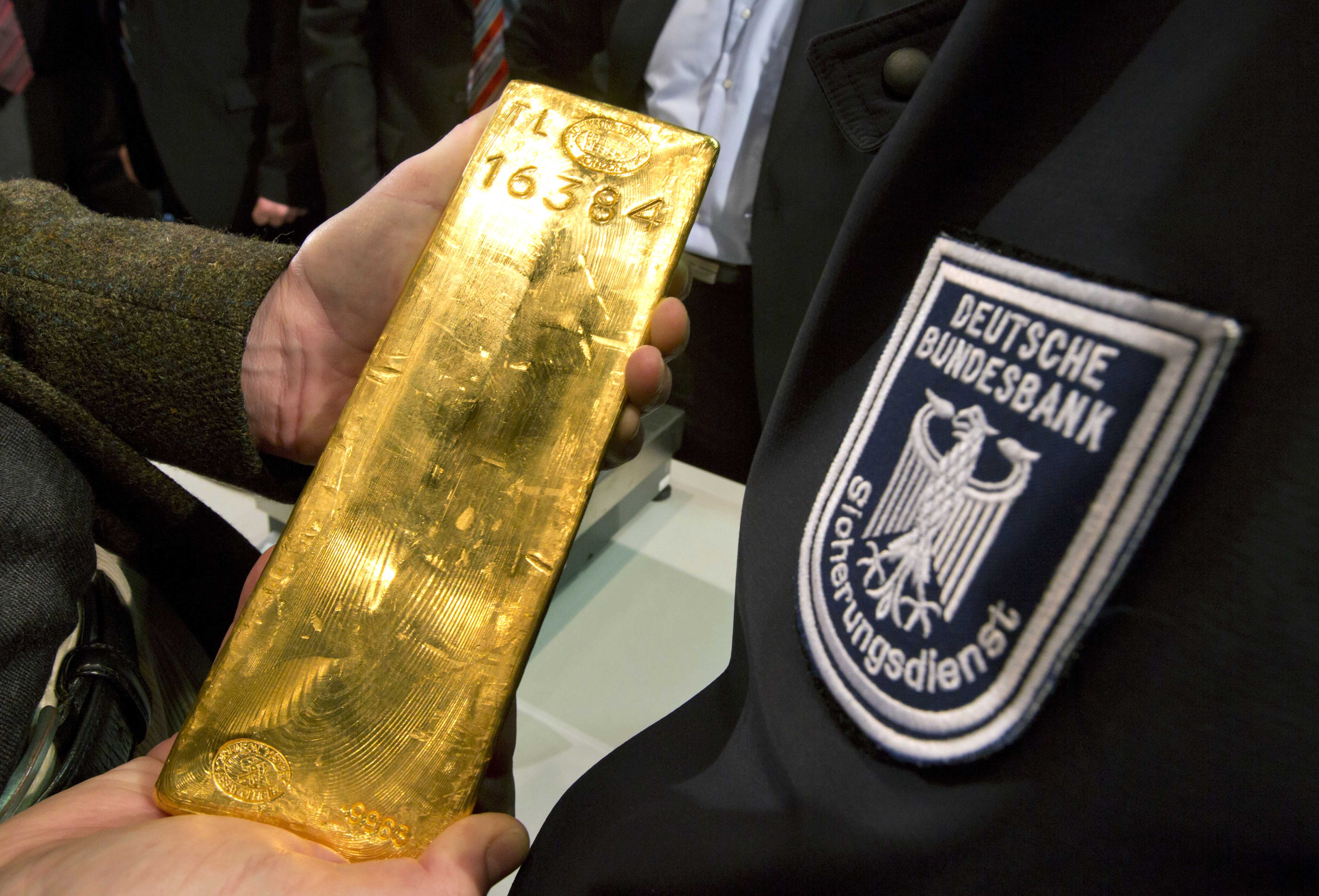 A journalist holds a gold ingot next to a security officer of the German Central Bank, right, in Frankfurt, Germany, Wednesday Jan. 16, 2013. Germany's central bank is to bring back home some US $36 billion ( 27 billion euro) worth of gold stored in the United States and France.The Bundesbank said in a statement Wednesday that it will repatriate all 374 tons of gold it had stored in Paris by 2020. An additional 300 tons - equivalent to 8 percent of the Bundesbank's total reserves worth about $183 billion _ will also be shipped from New York to Frankfurt. Frankfurt will hold half of Germany's 3,400 tons of gold by 2020, with New York retaining 37 percent and London storing 13 percent. The move follows criticism from Germany's independent Federal Auditors' Office last year bemoaning the central bank's oversight of gold reserves abroad. (AP Photo/dpa/ Frank Rumpenhorst)