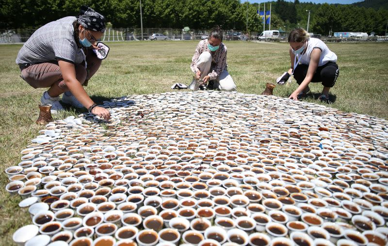 Artist Aida Sehovic helps sets up the installation of some 8,000 traditional ceramic cups filled with Bosnian coffee at the Potocari-Srebrenica Memorial Centre for victims of the 1995 massacre of Muslim men and boys by Serb forces