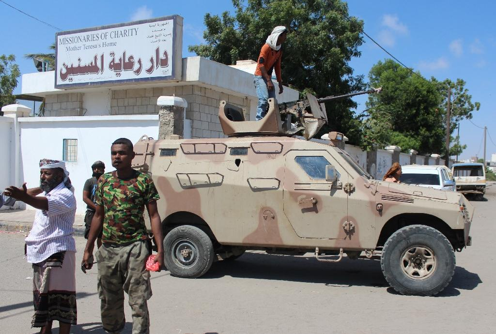Yemeni pro-government fighters gather outside an elderly care home in the southern city of Aden after it was attacked by gunmen on March 4, 2016, killing at least 16 people