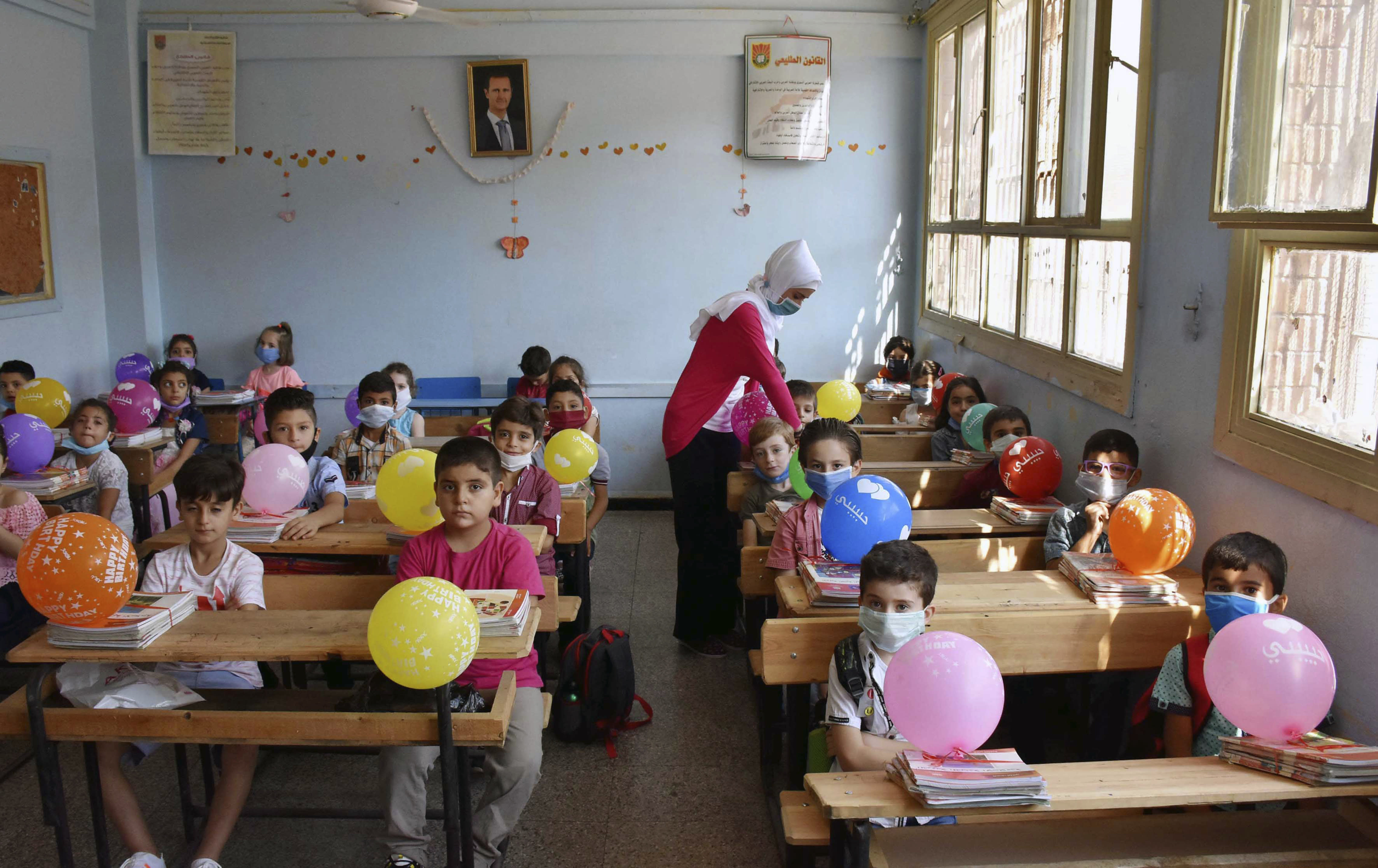 In this photo released by the Syrian official news agency SANA, students attend a lesson on their first day back at school, in Homs, Syria, Sunday, Sept. 13, 2020. More than 3 million students went to school in government-held areas around Syria Sunday marking the first school day amid strict measures to prevent the spread of coronavirus. (SANA via AP)