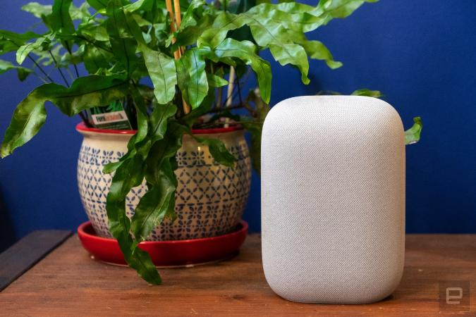 Google Nest Audio smart speaker sitting on a wooden tablet next to a green plant, against a blue wall.