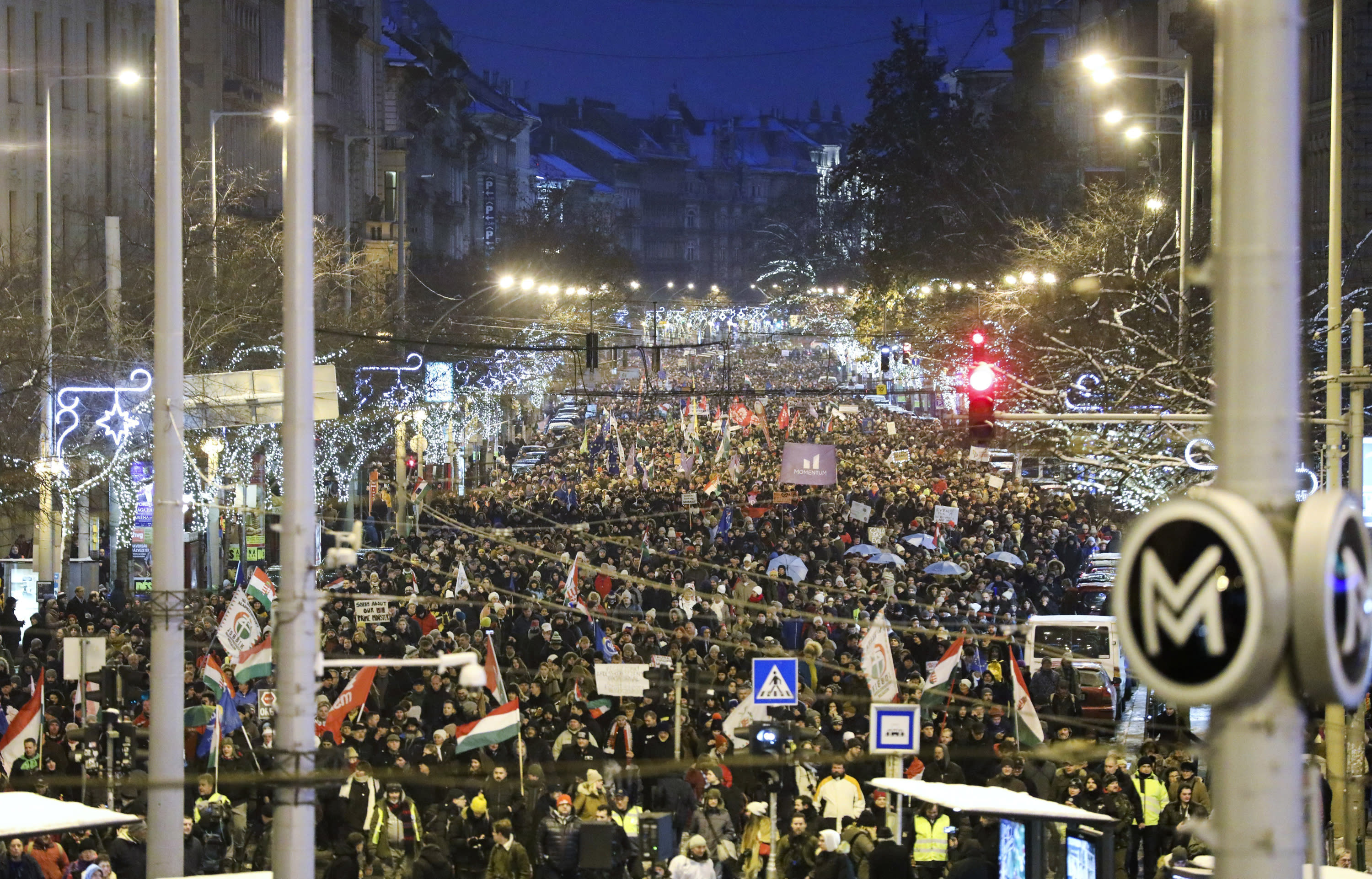 Anti-government demonstrators march under Christmas decorations in the city centre of Budapest, Hungary, Sunday, Dec. 16, 2018. Protesters are demonstrating against recent changes to the labour laws. (Balazs Mohai/MTI via AP)