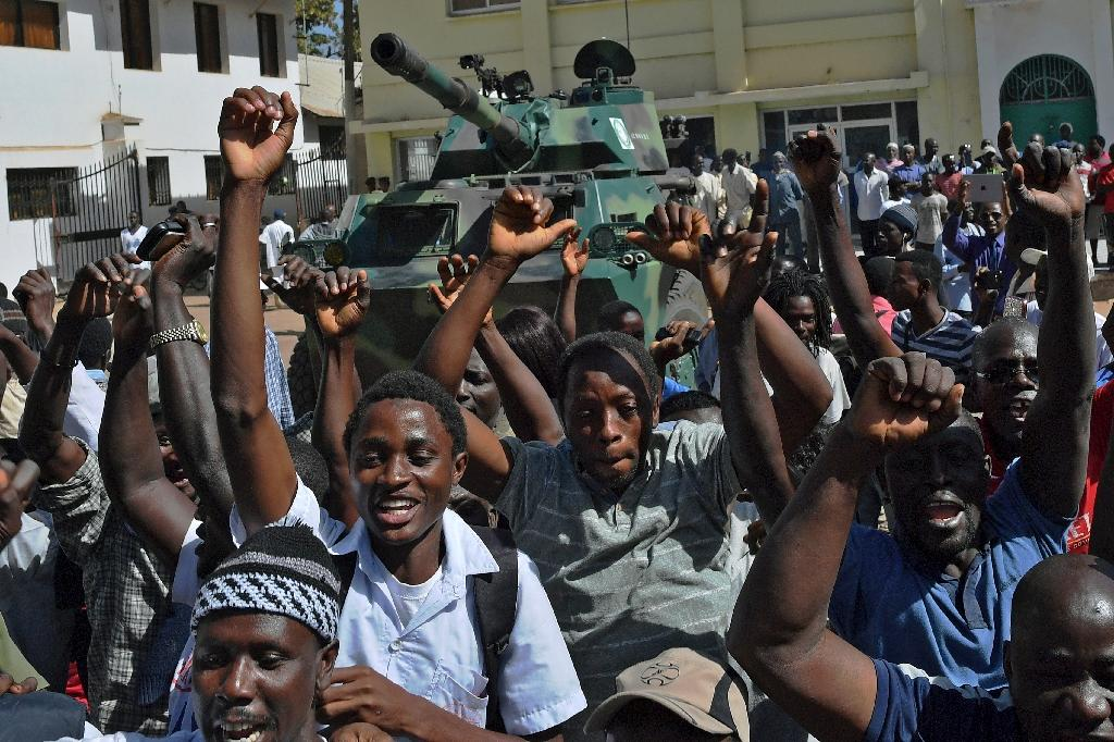 Gambians celebrate in front of an Economic Community of West African States armoured vehicle outside of the Statehouse in Banjul on January 23, 2017 (AFP Photo/CARL DE SOUZA)