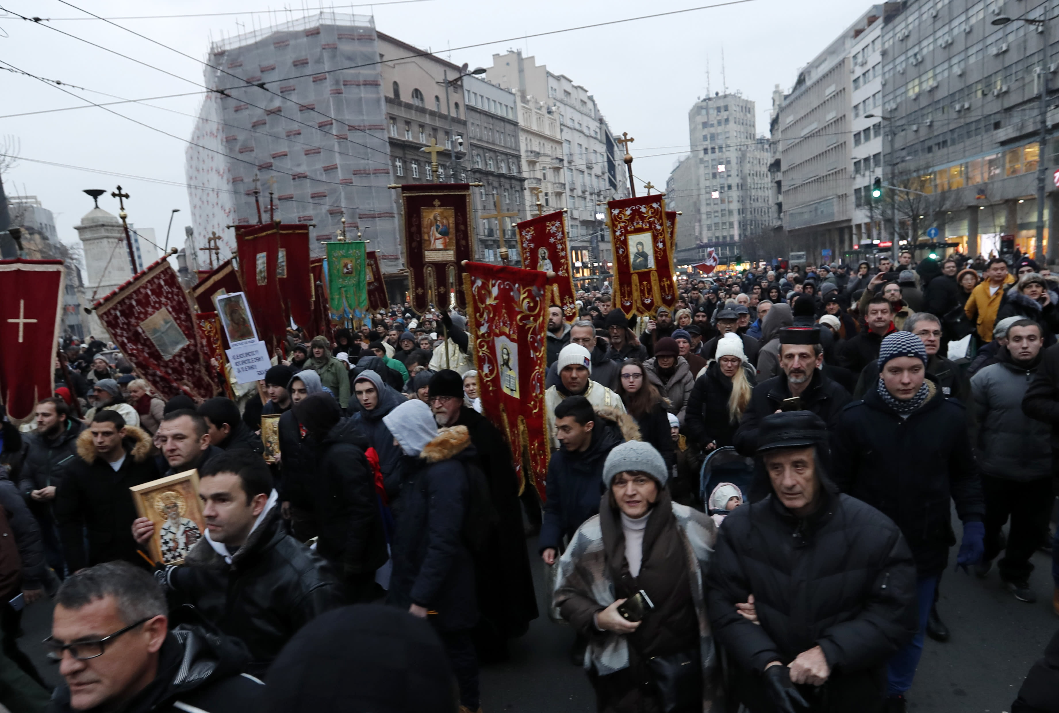 People hold Serbian church flags during a rally in central Belgrade, Serbia, Wednesday, Jan. 8, 2020. Thousands of Serbs have answered a call by the Serbian Orthodox Church to stage a protest against alleged suppression of religious and other rights of minority Serbs in neighboring countries. (AP Photo/Darko Vojinovic)