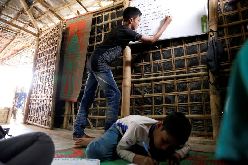 FILE PHOTO: Mohammed Tuahayran teaches English in a makeshift school at Kutupalong refugee camp in Cox's Bazar