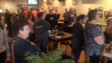 Customers at packed restaurant all stand and join in as local high school choir sings national anthem