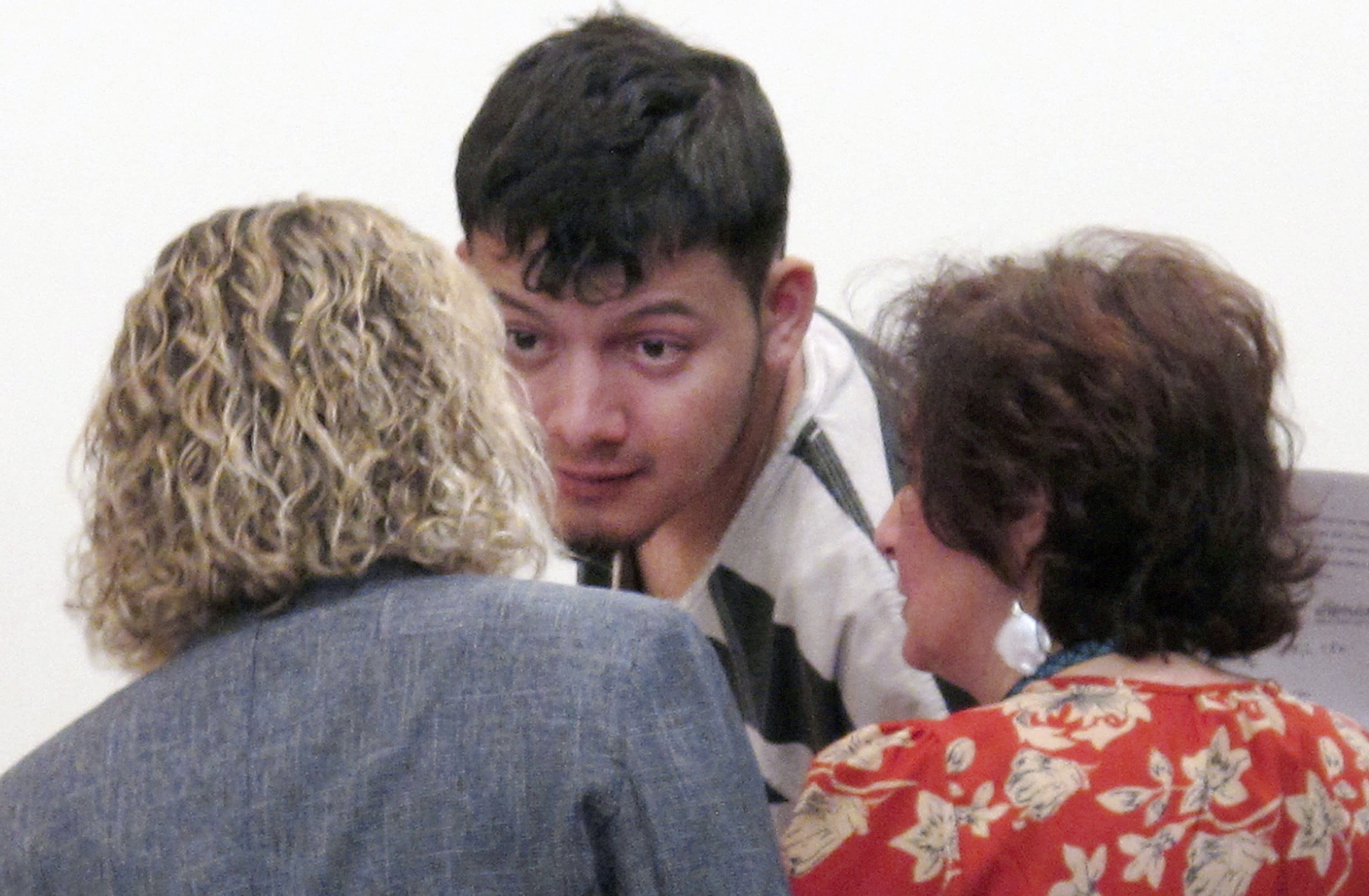 """FILE - In this Jan. 24, 2019 file photo, Wilber Ernesto Martinez-Guzman, 19, of El Salvador, talks to his public defender and interpreter during his initial appearance in Carson City Justice Court in Carson City, Nev. A detective says the Salvadoran immigrant charged with four Nevada murders told police he robbed and killed his elderly victims during a 10-day rampage in January because he needed money to buy methamphetamine. According to a grand jury transcript obtained by The Associated Press, the Reno detective testified last week that Martinez-Guzman broke into tears and repeatedly called himself an """"idiot"""" before confessing to the murders. (AP Photo/Scott Sonner, File)"""