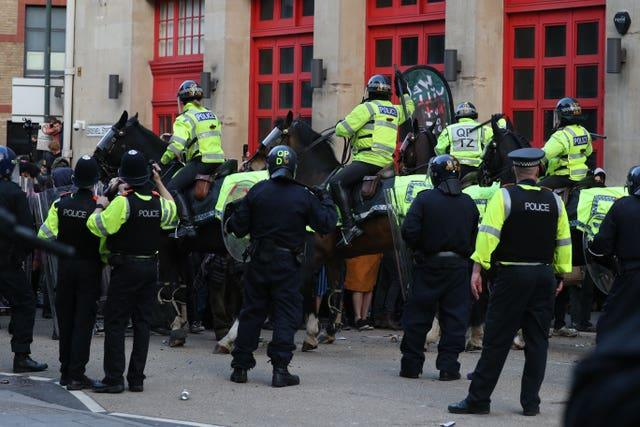 Police horses are deployed as they hold back people outside Bridewell police station in Bristol