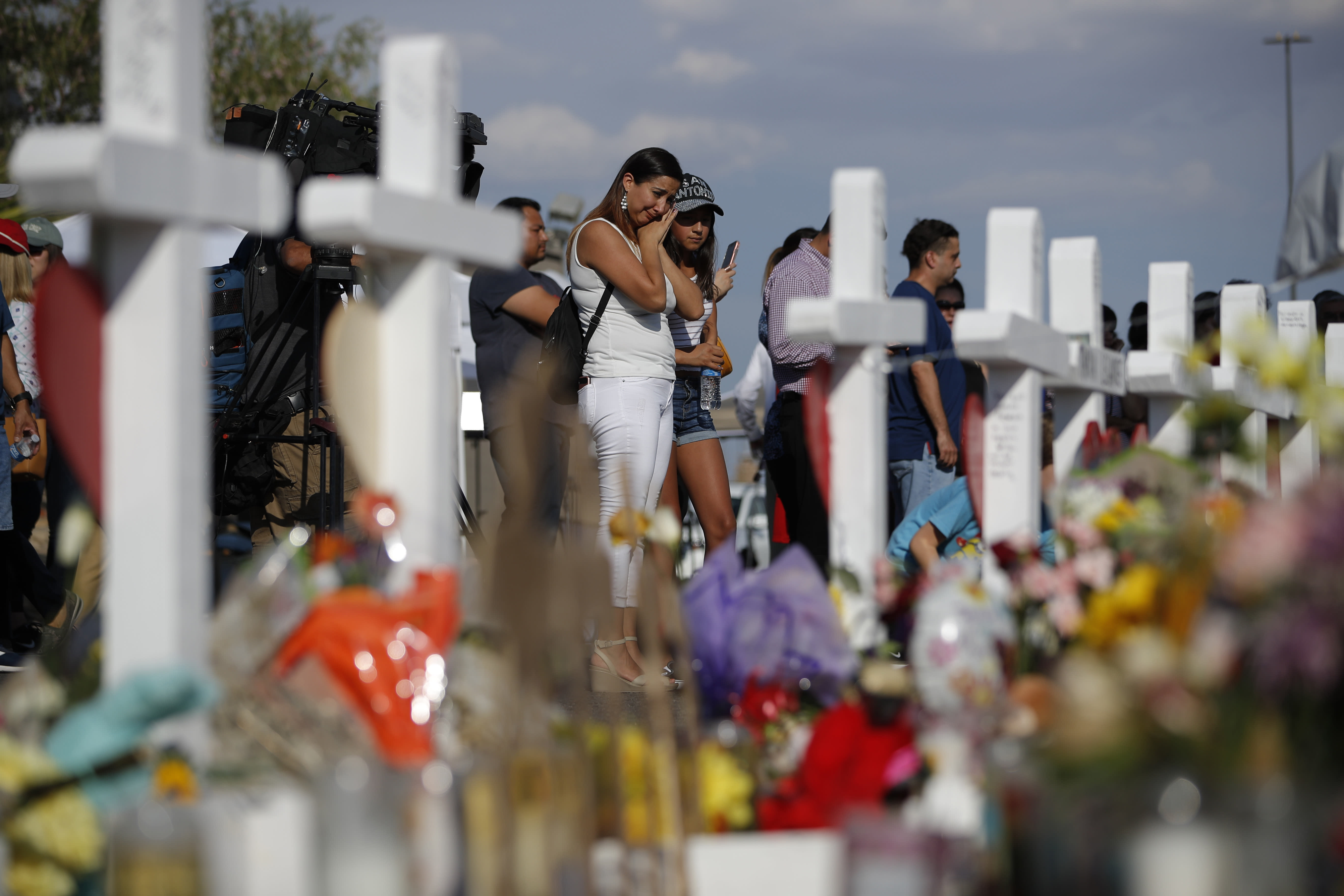 People visit a makeshift memorial, Monday, Aug. 5, 2019, at the site of a mass shooting at a shopping complex, in El Paso, Texas. (AP Photo/John Locher)