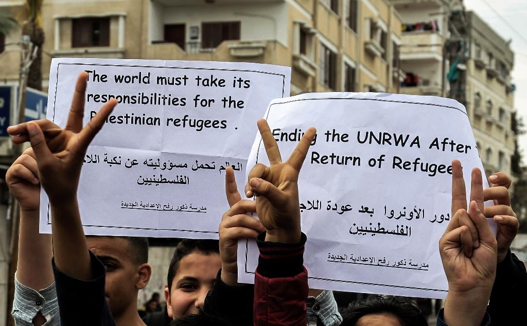 Palestinian school students at the Rafah refugee camp in the Gaza Strip shout slogans and hold signs protesting the US move to freeze funding for the UN agency for Palestinian refugees in March 2018