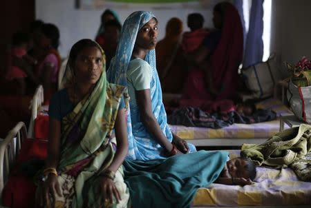 Bai, who underwent a sterilisation surgery at a government mass sterilisation camp, watches while other women sit inside a hospital at Bilaspur district in Chhattisgarh