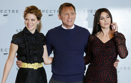 """Actors Lea Seydoux, Daniel Craig and Monica Bellucci pose on stage during an event to mark the start of production for the new James Bond film """"Spectre"""" at Pinewood Studios"""