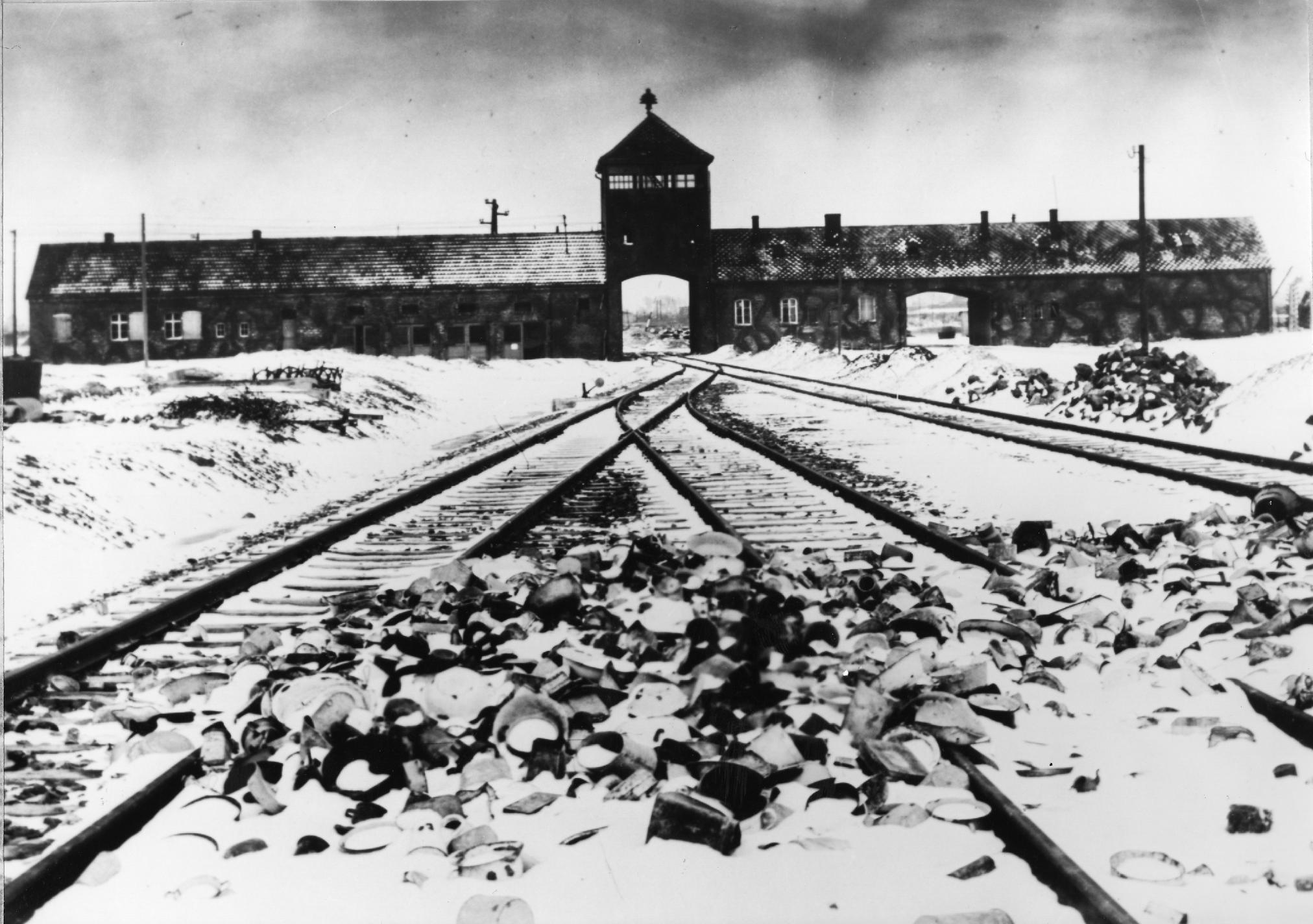 """FILE - This January 1941 file photo shows entry to the concentration camp Auschwitz-Birkenau in Poland, with snow-covered railtracks leading to the camp. The Auschwitz-Birkenau camp was the largest camp where people were terminated during the fascist regime rule of dictator Adolf Hitler over Germany during World War II. Germany has launched a war crimes investigation against an 87-year-old Philadelphia man it accuses of serving as an SS guard at the Auschwitz death camp, The Associated Press has learned, following years of failed U.S. Justice Department efforts to have the man stripped of his American citizenship and deported. Johann """"Hans"""" Breyer, a retired toolmaker, admits he was a guard at Auschwitz during WWII, but told the AP he was stationed outside the facility and had nothing to do with the wholesale slaughter of some 1.5 million Jews and others behind the gates. (AP Photo/File)"""