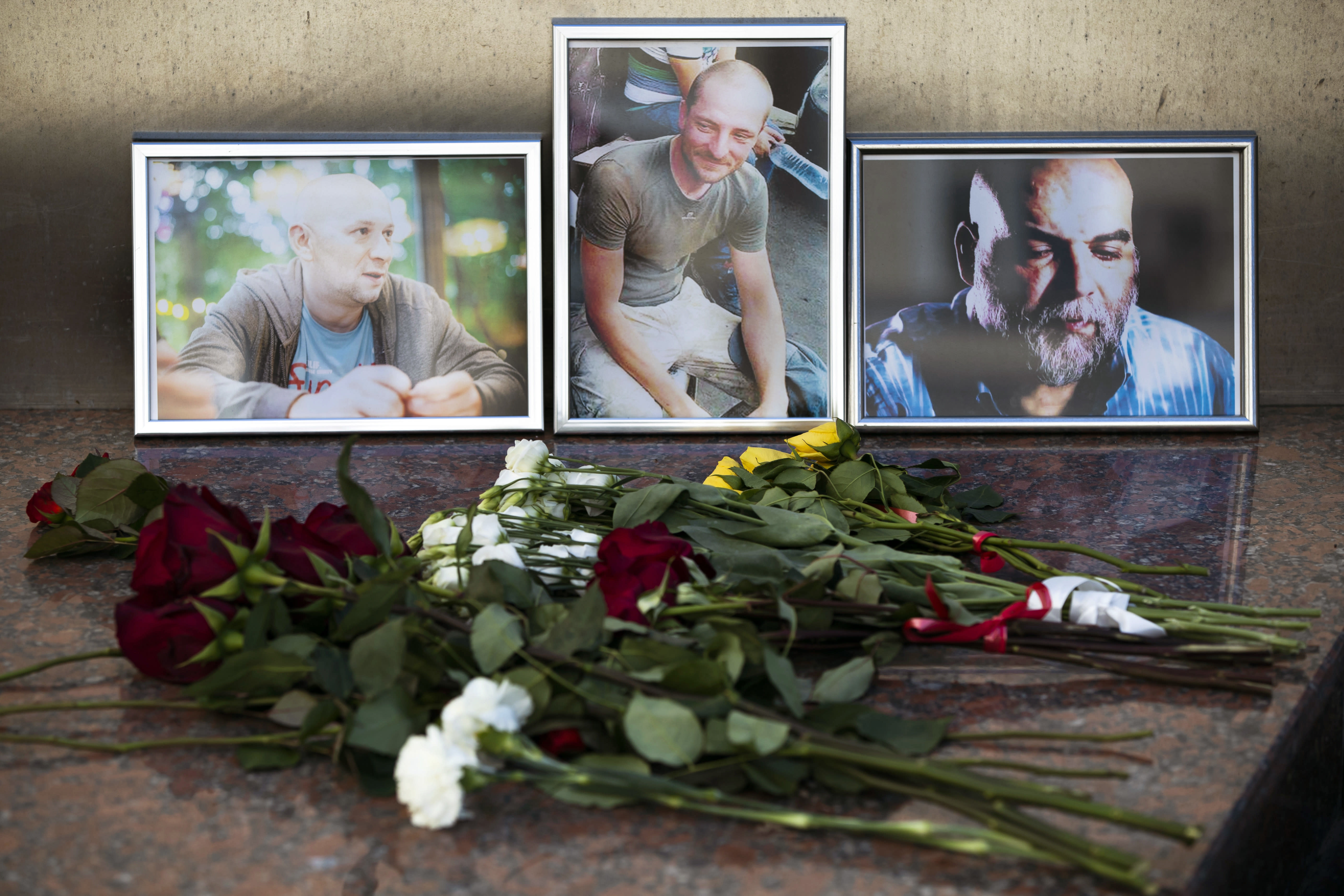 Flowers are placed by portraits of slain journalists Alexander Rastorguyev, Kirill Radchenko and Orkhan Dzhemal, at the Russian journalists Union building in Moscow, Russia, Wednesday, Aug. 1, 2018. Russian journalists who were killed in the Central African Republic had been working on an investigation into Russian private military contractors and the mining industries there, their editor said Wednesday. (AP Photo/Pavel Golovkin)