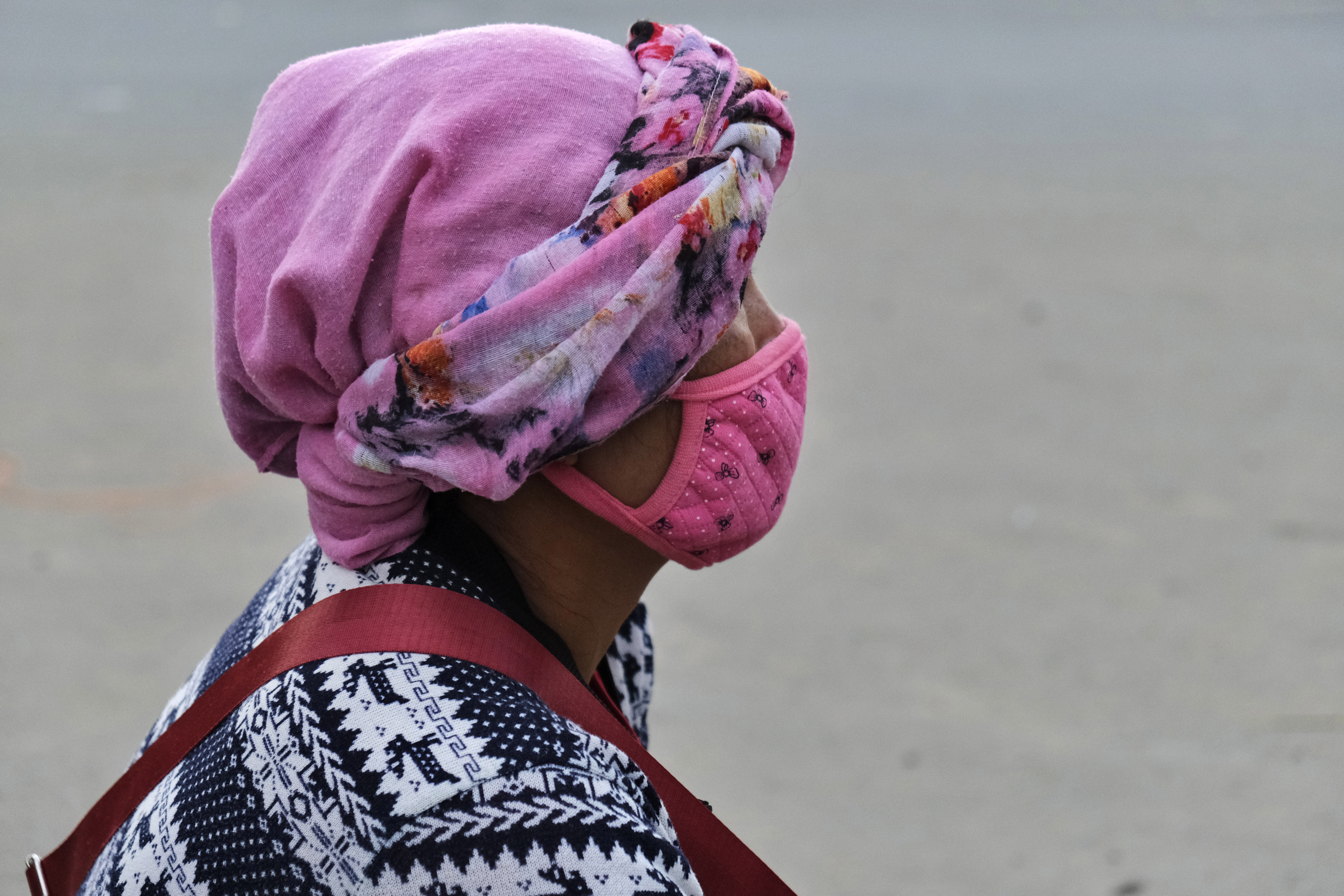 A Naga woman wears a face mask and sits by the side of a road selling poultry in Kohima, capital of the northeastern Indian state of Nagaland, Saturday, Aug. 8, 2020. As India hit another grim milestone in the coronavirus pandemic on Friday, crossing 2 million confirmed cases and more than 41,000 deaths, community health volunteers went on strike complaining they were ill-equipped to respond to the wave of infection in rural areas. (AP Photo/Yirmiyan Arthur)