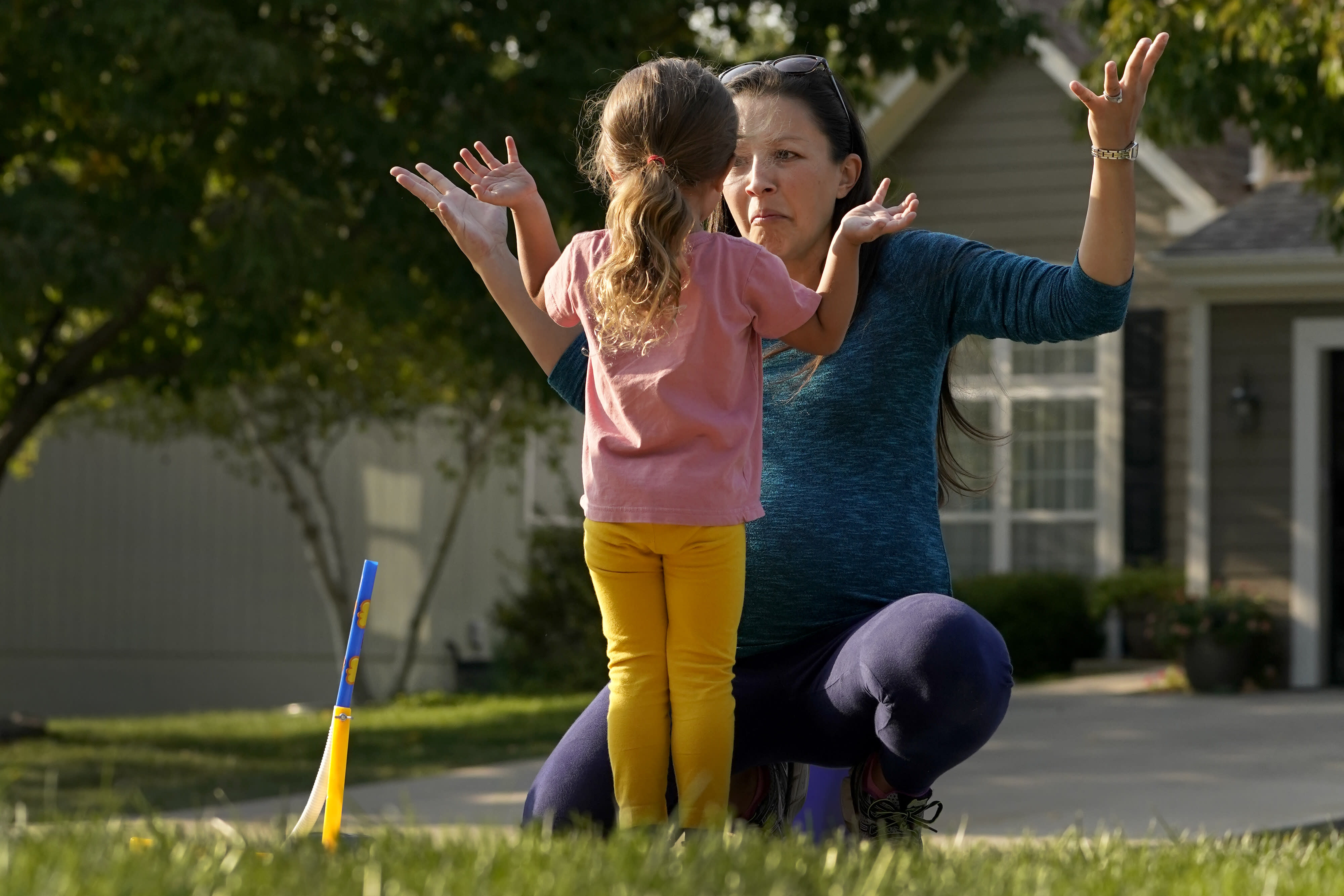 Claire Reagan plays with her daughter Abbie, 3, Monday, Sept. 21, 2020, outside her home in Olathe, Kan. Reagan is keeping her son Evan, 5, from starting kindergarten and her daughter from preschool due to concerns about the coronavirus pandemic. (AP Photo/Charlie Riedel)