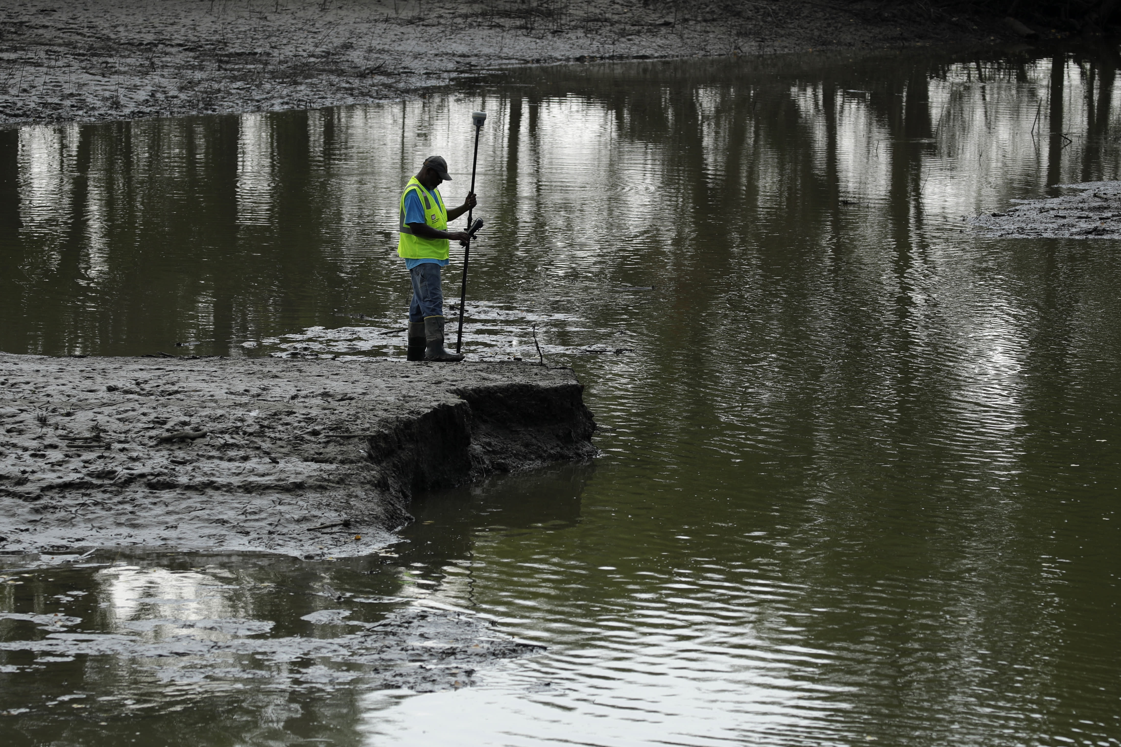 FILE - In this Aug. 6, 2019, file photo, U.S. Army Corps of Engineers worker Ron Allen uses a GPS tool to survey the extent of damage where a levee failed along the Missouri River near Saline City, Mo. The National Weather Service said Thursday, Feb. 13, 2020, there is an elevated flood risk along the eastern Missouri River basin this spring because the soil remains wet and significant snow is on the ground in North Dakota and South Dakota. (AP Photo/Charlie Riedel, File)