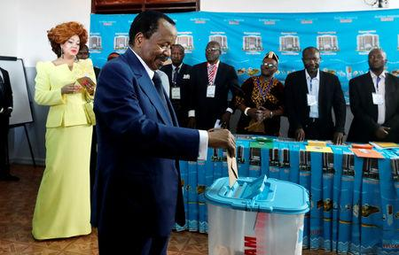 FILE PHOTO: Cameroonian President Paul Biya casts his ballot while his wife Chantal watches during the presidential election in Yaounde