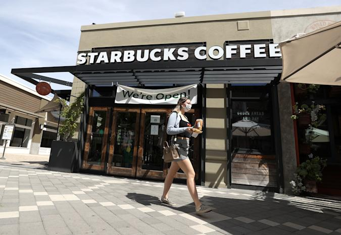 CORTE MADERA, CALIFORNIA - JUNE 10: A customer walks by a Starbucks Coffee store on June 10, 2020 in Corte Madera, California. Starbucks announced plans to close 400 of its company owned cafes over the next 18 months as the coffee shop chain estimates losing over $3 billion due to the coronavirus COVID-19 pandemic. (Photo by Justin Sullivan/Getty Images)