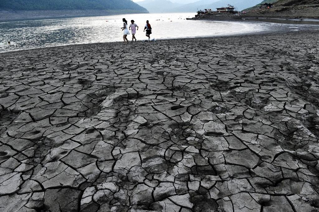 People walk along a dried and cracked river beach of the Yangtze River in China (AFP Photo/)