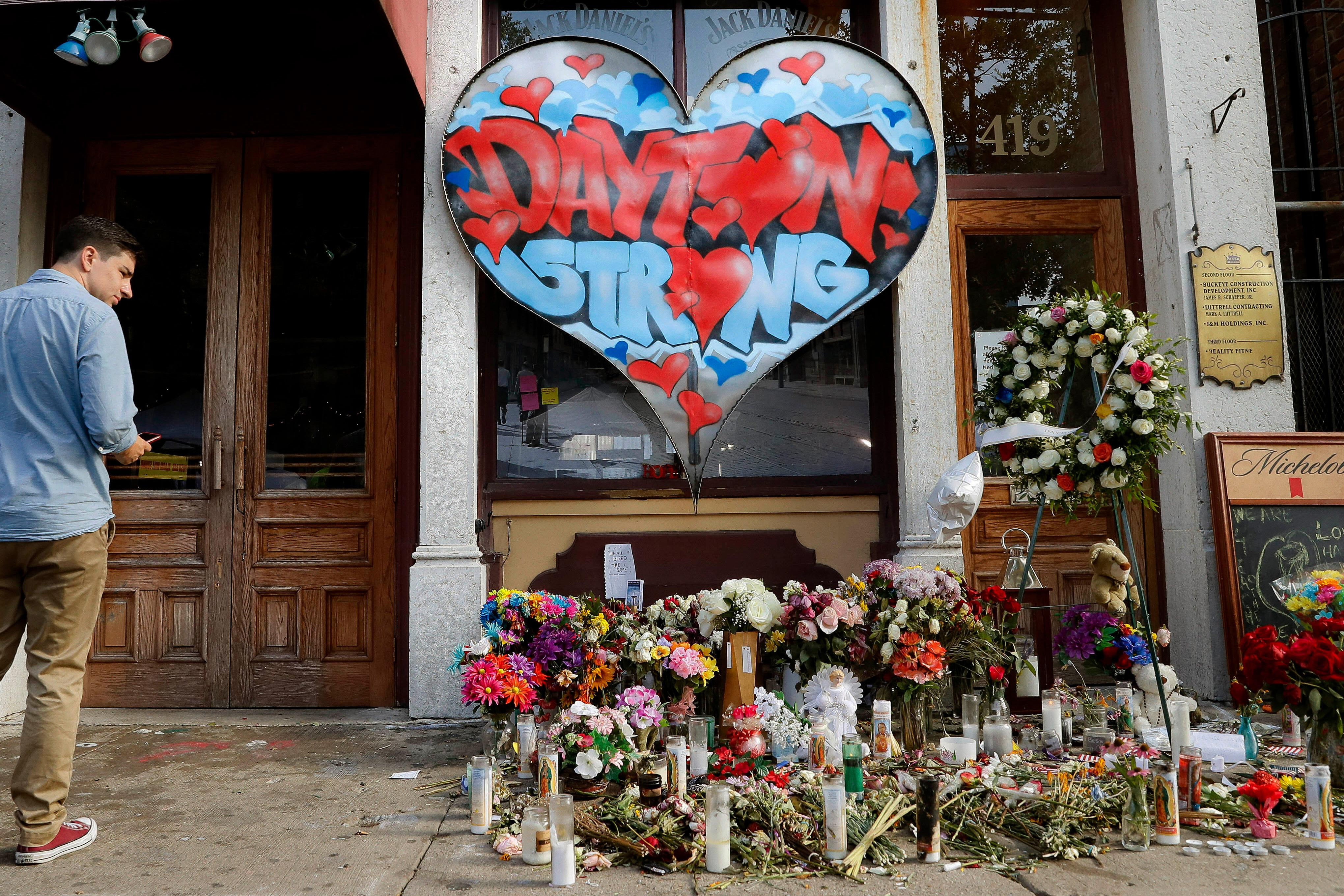 """FILE - In this Aug. 7, 2019 file photo, a pedestrian passes a makeshift memorial for the slain and injured victims of a mass shooting that occurred in the Oregon District early Sunday morning in Dayton, Ohio. Ever since """"Boston Strong"""" became a rallying cry after the Boston Marathon bombing, the idea of """"strong"""" has become an inescapable part of how this country heals after tragedy. (AP Photo/John Minchillo, File)"""