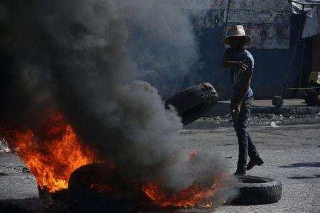 A supporter of ex-president Jean-Bertrand Aristide's Fanmi Lavalas Party throws a tyre into the fire during a protest as preliminary results declared businessman Jovenel Moise the official winner of the November 2016 presidential elections in Port-au-Prince, Haiti, January 3, 2017. REUTERS/Jeanty Junior Augustin