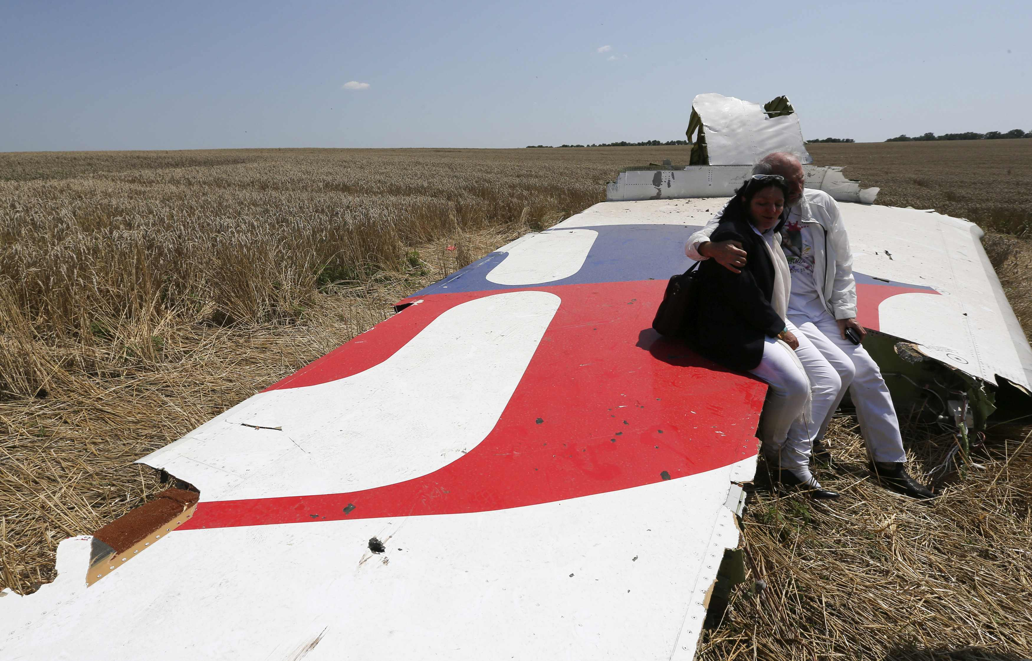 George and Angela Dyczynski sit on a piece of wreckage of the downed Malaysia Airlines Flight MH17, during their visit to the crash site near the village of Hrabove (Grabovo), in Donetsk region in this July 26, 2014 file photo. The 19,500 staff of Malaysia Airlines (MAS) face a new ordeal - a quarter of them may lose their jobs at the unprofitable airline, hit by two jet disasters this year. Flight MH370 remains untraced since its disappearance en route from Kuala Lumpur to Beijing in March. REUTERS/Sergei Karpukhin (UKRAINE - Tags: POLITICS DISASTER TRANSPORT CIVIL UNREST)