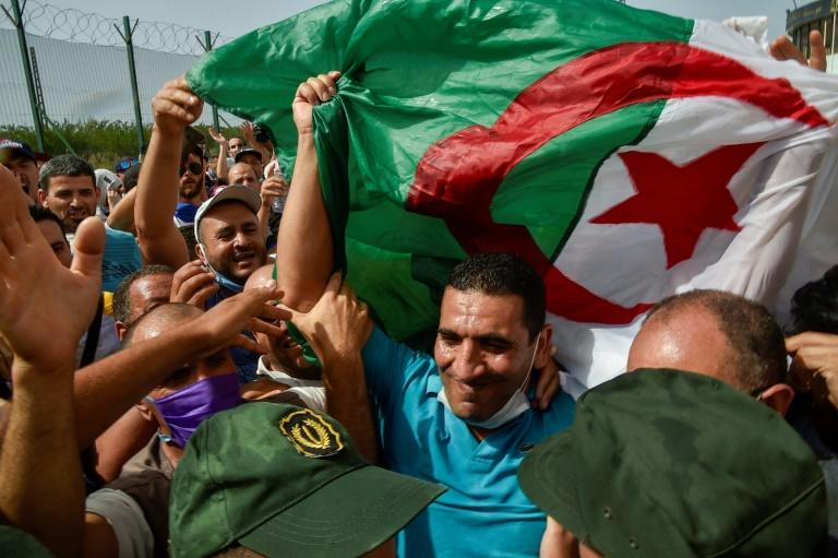 """Karim Tabbou, one of the most prominent figures of Algeria's anti-government """"Hirak"""", is greeted by supporters after his provisional release from jail on July 2, 2020 (AFP Photo/RYAD KRAMDI )"""
