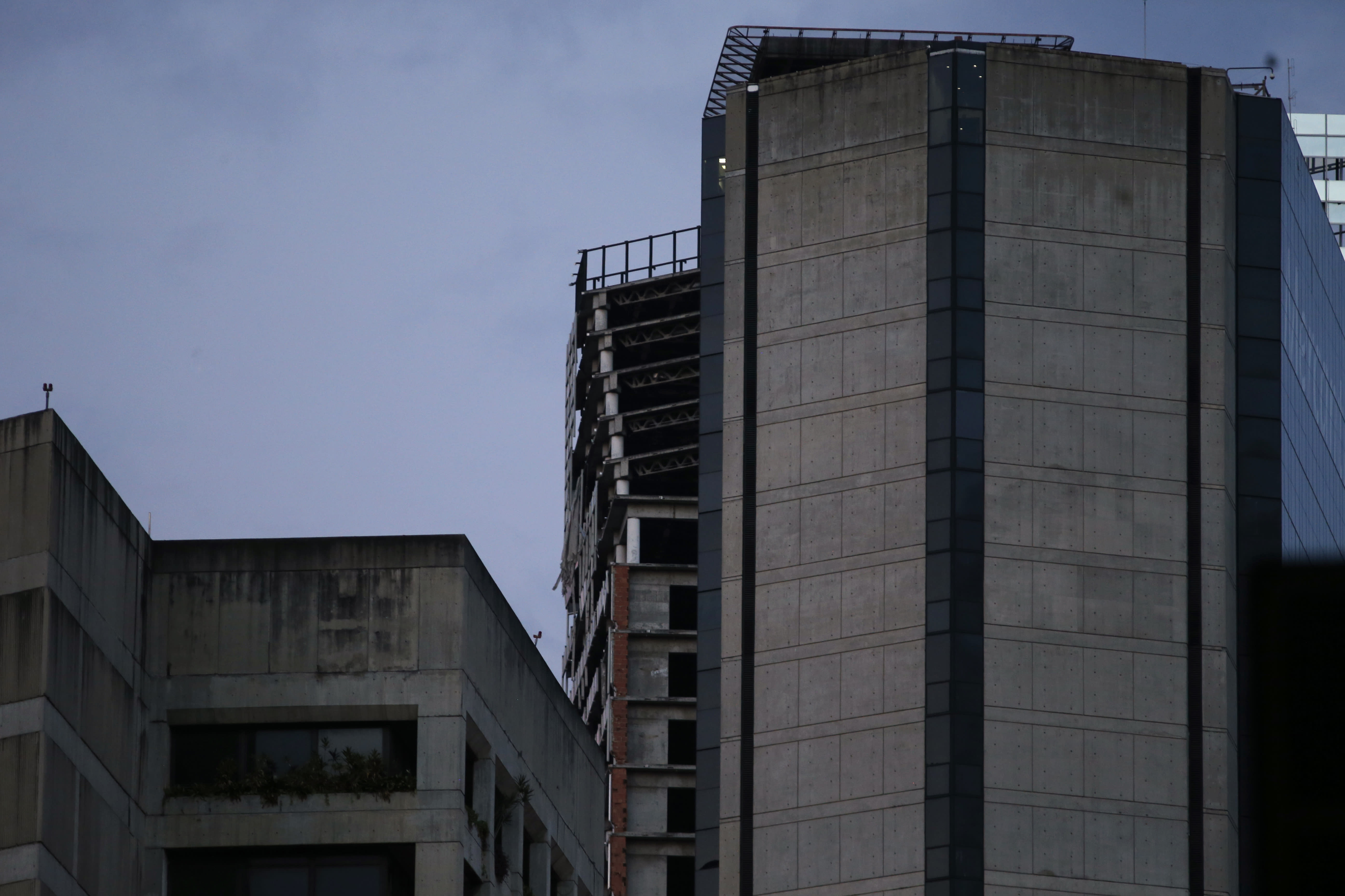 """An abandoned, unfinished skyscraper known as """"The Tower of David"""" shows an inclination on the top floors where the columns are exposed, top center, after a powerful earthquake shook eastern Venezuela, causing buildings to be evacuated in the capital of Caracas, Venezuela, Tuesday, Aug. 21, 2018. The quake was felt as far away as Colombia's capital and in the Venezuelan capital office workers evacuated buildings and people fled homes. (AP Photo/Ariana Cubillos)"""