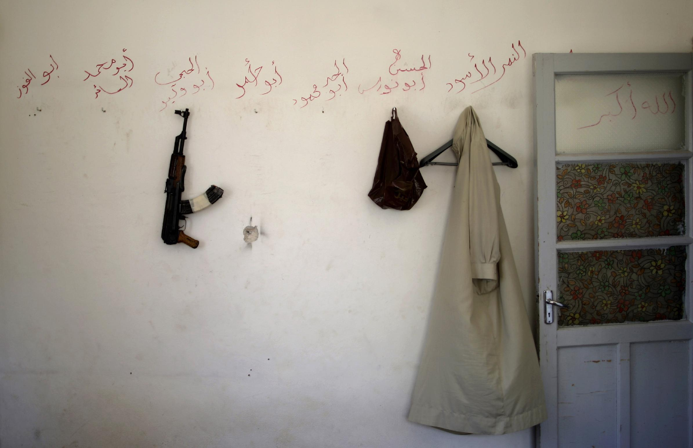 """In this Tuesday, Sept. 4, 2012 photo, a shirt and an AK-47 of a rebel fighter hang on a wall inside their headquarters in Marea, on the outskirts of Aleppo, Syria. Arabic reads on the wall from right, """"God is great, the black panther, Alhassan Abu Nawras, Abu Mahmoud, Abu Ahmad, Abu Walid, Abu Mohammed, Abu Alfoaz."""" Rebels have taken a major stride in uniting their ranks in the battle for Syria's largest city, giving them hope they could tip the balance in three-months of bloody stalemate in Aleppo, one of the biggest prizes of the civil war.. The question is how much more destruction the city can bear. Regime troops are retaliating with heavier bombardment, and civilians are bearing the brunt, their neighborhoods left in rubble. (AP Photo/Muhammed Muheisen)"""