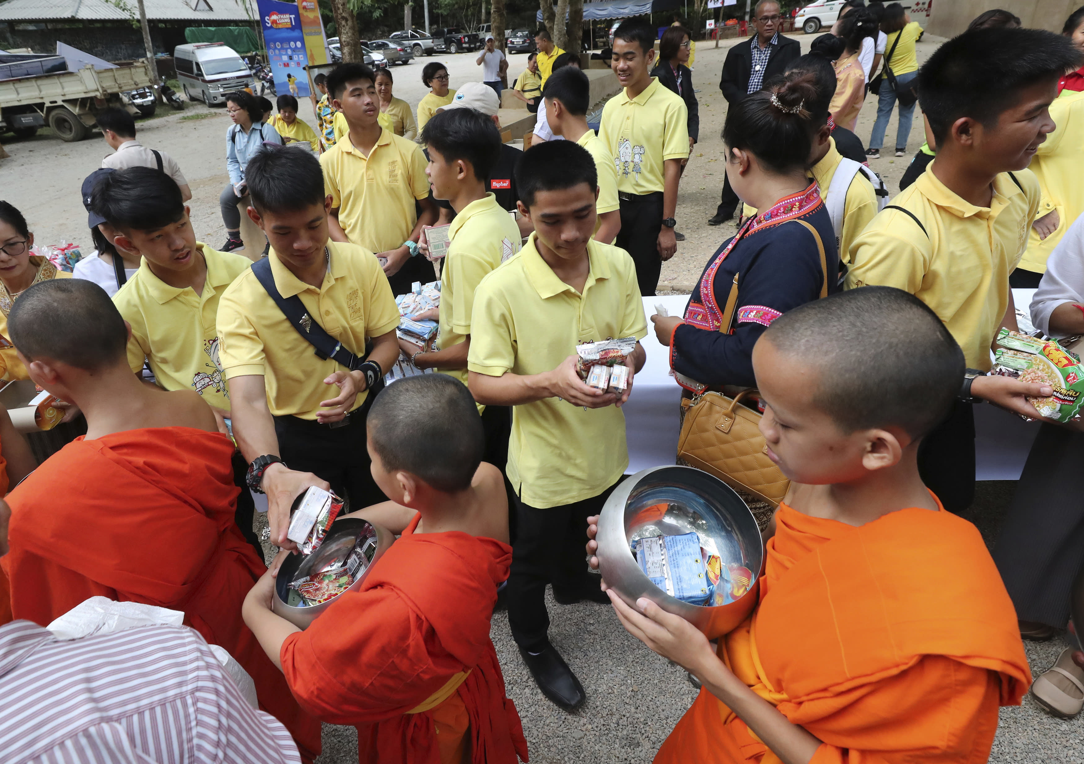 Members of the Wild Boars soccer team who were rescued from a flooded cave, offer foods to Buddhist monks near the Tham Luang cave in Mae Sai, Chiang Rai province, Thailand Monday, June 24, 2019. The 12 boys and their coach attended a Buddhist merit-making ceremony at the Tham Luang to commemorate the one-year anniversary of their ordeal that saw them trapped in a flooded cave for more than two weeks. (AP Photo/Sakchai Lalit)