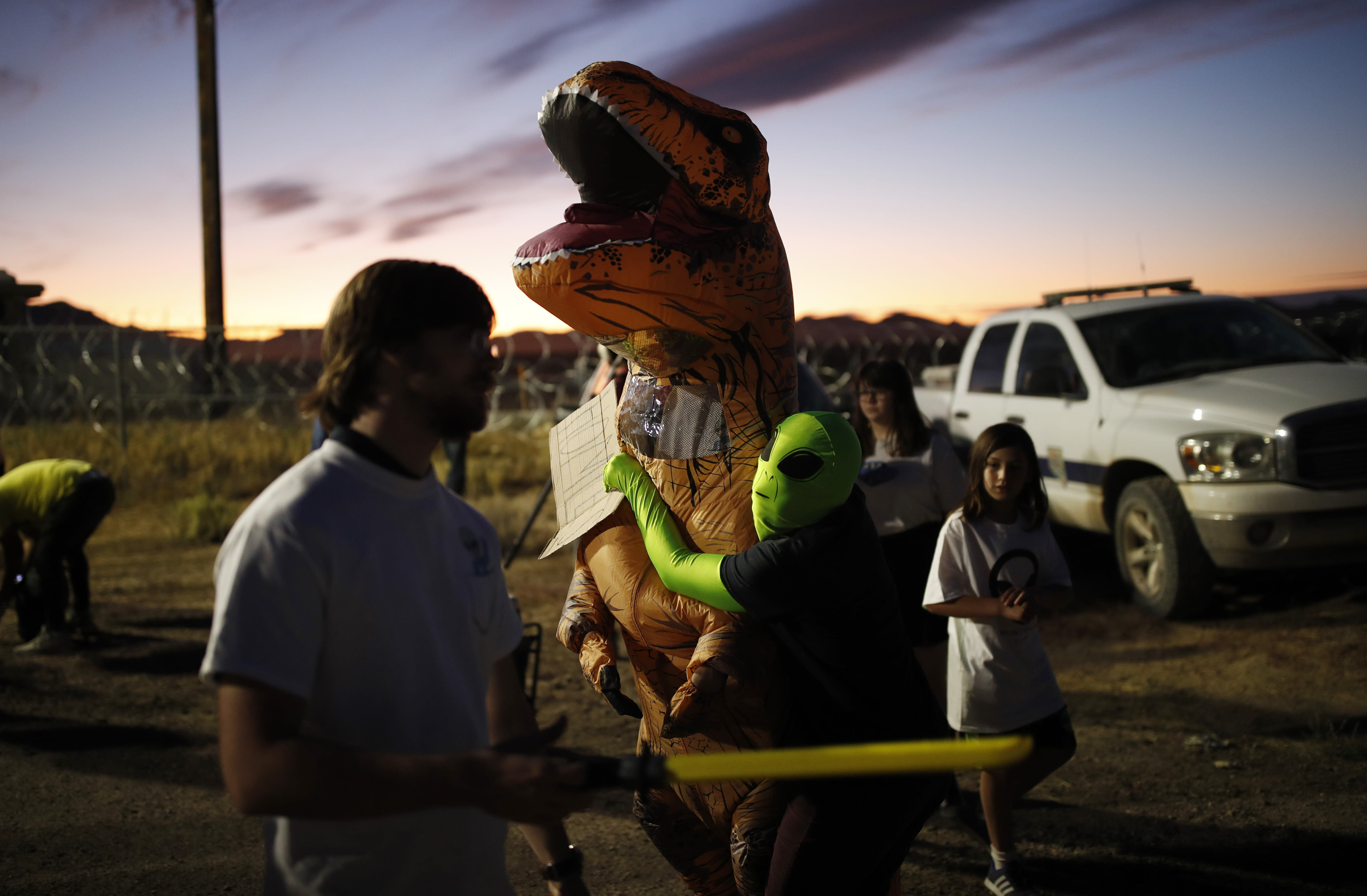 """People dressed in costumes visit an entrance to the Nevada Test and Training Range near Area 51, Friday, Sept. 20, 2019, near Rachel, Nev. People came to visit the gate inspired by the """"Storm Area 51"""" internet hoax. (AP Photo/John Locher)"""