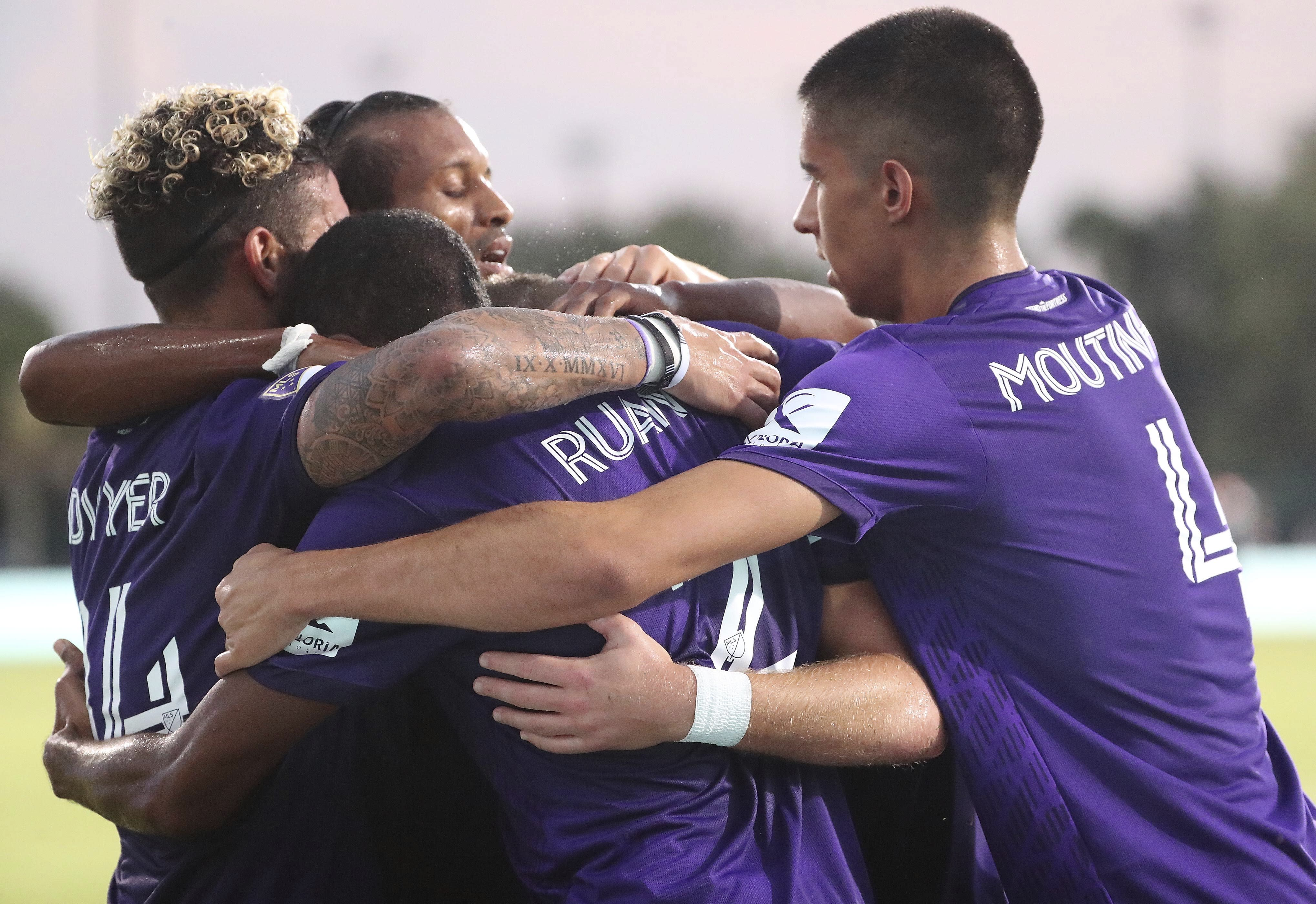 Orlando players celebrate after Chris Mueller, hidden at center, scored a goal against New York City FC during the MLS is Back tournament soccer match, Tuesday, July 14, 2020, in Lake Buena Vista, Fla. (Stephen M. Dowell/Orlando Sentinel via AP)