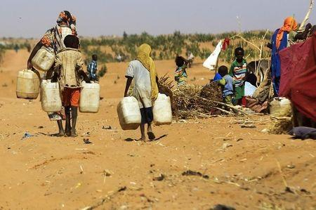 People walk to fill water containers at the Zamzam IDP camp in North Darfur