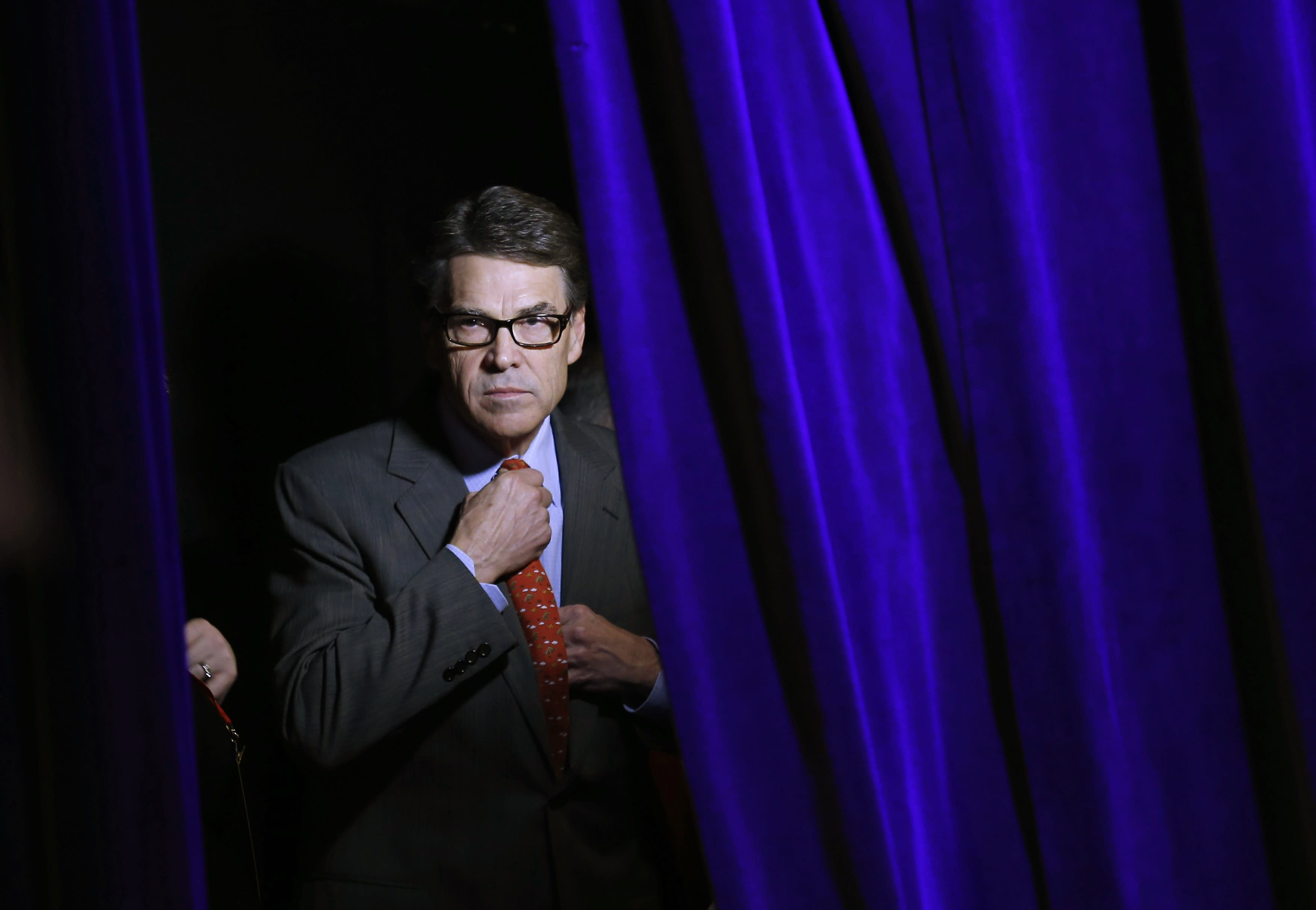 Former Governor of Texas Rick Perry adjusts his tie as he listens to his introduction from the side of the stage at the Freedom Summit in Des Moines, Iowa, January 24, 2015. REUTERS/Jim Young (UNITED STATES - Tags: POLITICS)
