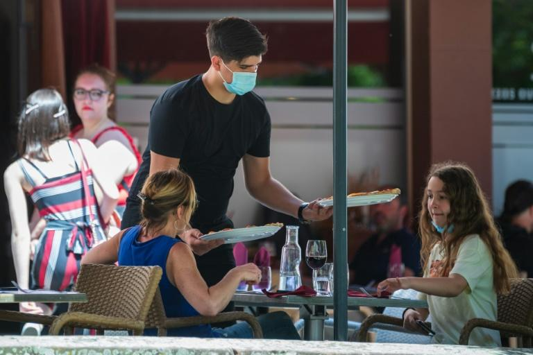 A waiter, wearing a face mask, served customers on a restaurant's terrace in Strasbourg, eastern France, on Tuesday. (AFP Photo/PATRICK HERTZOG)