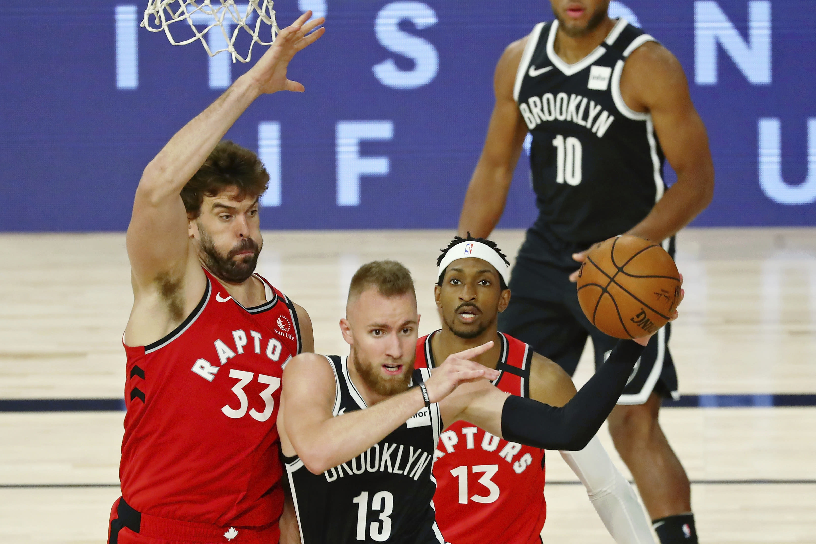 Brooklyn Nets guard Dzanan Musa (13) passes the ball while defended by Toronto Raptors center Marc Gasol (33) during the second half in Game 3 of an NBA basketball first-round playoff series, Friday, Aug. 21, 2020, in Lake Buena Vista, Fla. (Kim Klement/Pool Photo via AP)
