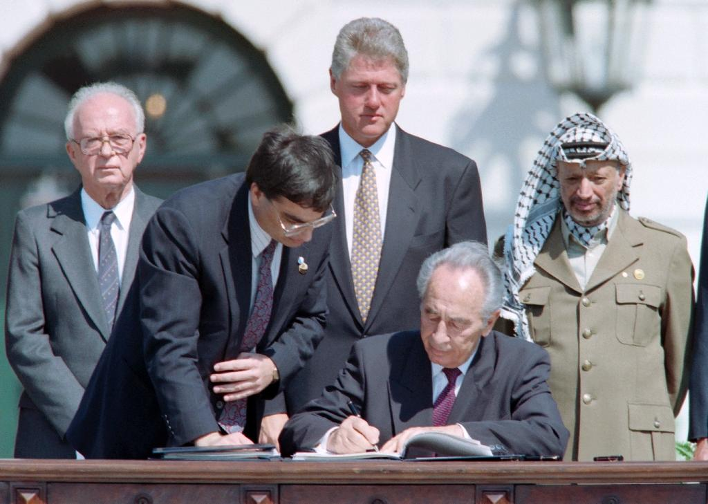 Israeli foreign minister Shimon Peres signs the Oslo Accords on September 13, 1993 in a ceremony at the White House (AFP Photo/J. DAVID AKE)