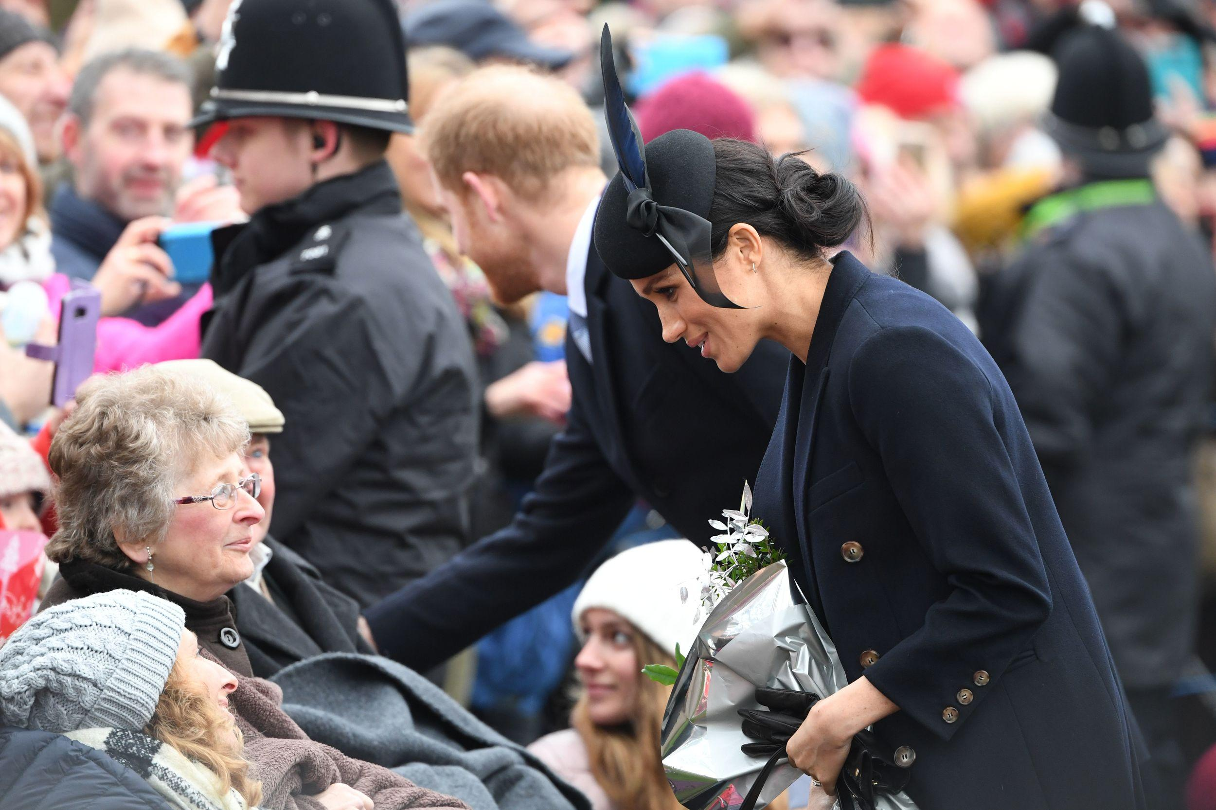 Meghan, Duchess of Sussex and Britain's Prince Harry, Duke of Sussex,   greet wellwishers after the Royal Family's traditional Christmas Day service at St Mary Magdalene Church in Sandringham, Norfolk, eastern England, on December 25, 2018. (Photo by Paul ELLIS / AFP)        (Photo credit should read PAUL ELLIS/AFP/Getty Images)