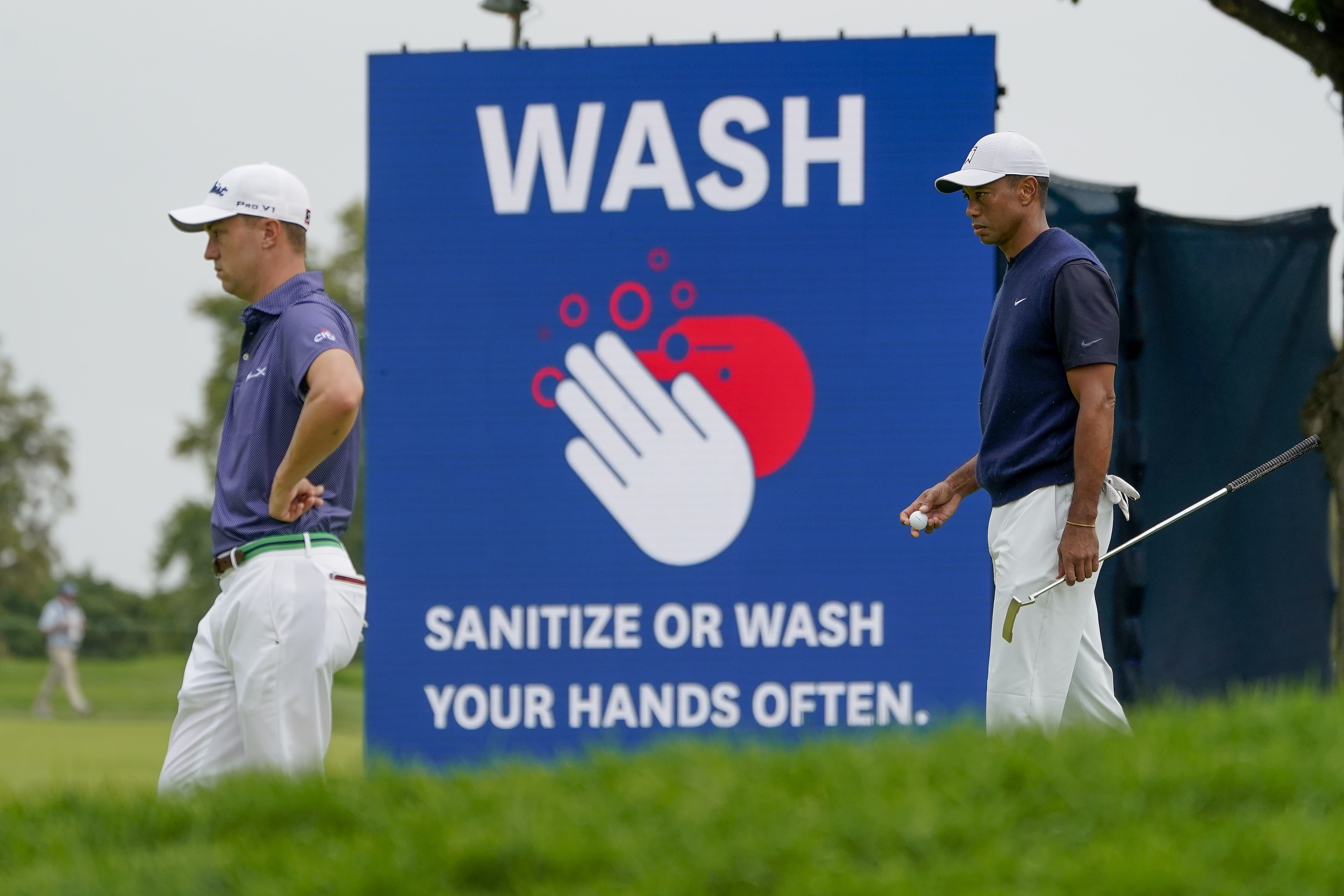 Justin Thomas, of the United States, left, and Tiger Woods, of the United States, wait to putt on the 17th green during the first round of the US Open Golf Championship, Thursday, Sept. 17, 2020, in Mamaroneck, N.Y. (AP Photo/Charles Krupa)