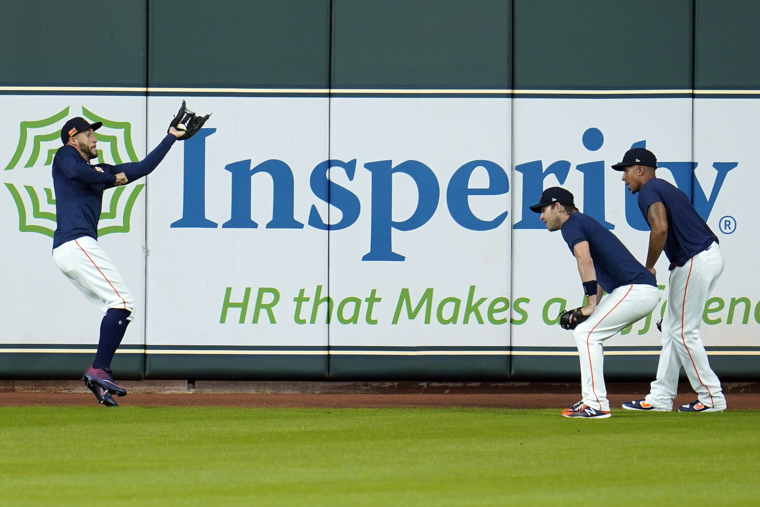 Houston Astros center fielder George Springer, left, makes a catch as outfielders Josh Reddick, center, and Michael Brantley watch during a baseball practice at Minute Maid Park, Sunday, July 5, 2020, in Houston. (AP Photo/David J. Phillip)
