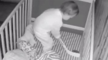 Toddler caught on camera playing hockey in his crib